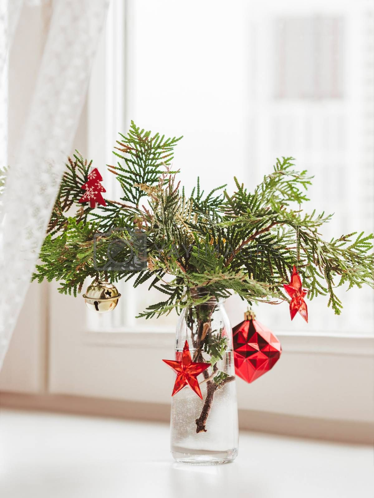 Vase with decorated thuja branches stands on window sill. Sustainable alternative for Christmas tree. Caring for nature. Refusal to cut down spruce forests. New Year celebration.