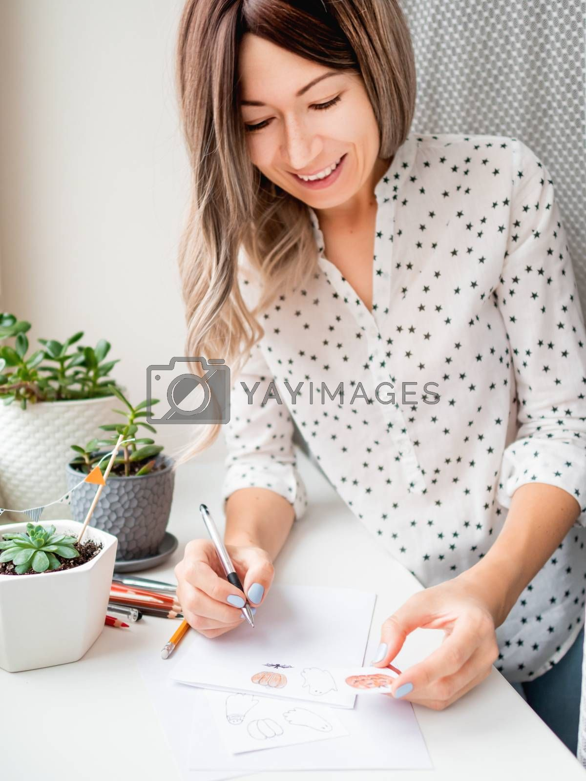 Woman decorates flower pots with handmade Halloween stickers. Hand drawn ghosts, flags and pumpkins in flower pot with succulent plant.