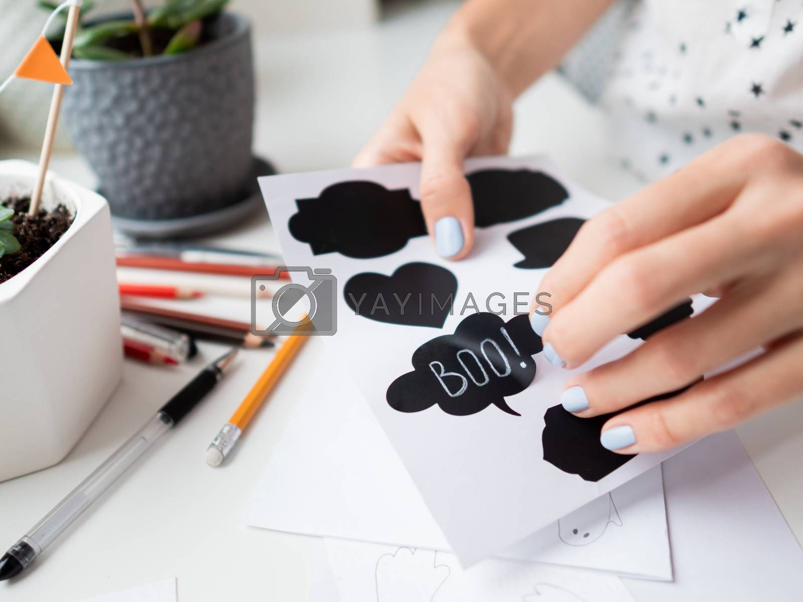 Woman writes Boo! on decorative black stickers for chalks. Handmade decorations for Halloween.