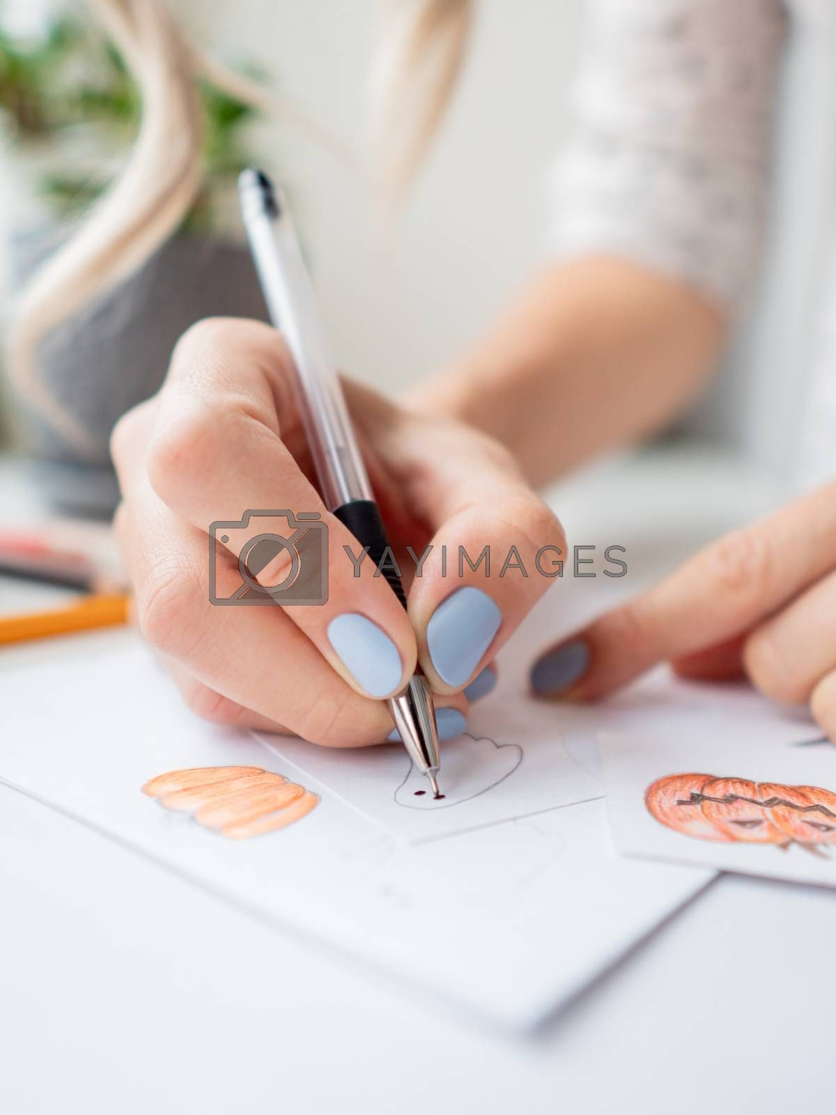 Woman with blue polish on nails draw ghosts and pumpkins. Handmade decorations for Halloween. DIY stickers on for flower pots. Socially-Distanced Halloween at home.