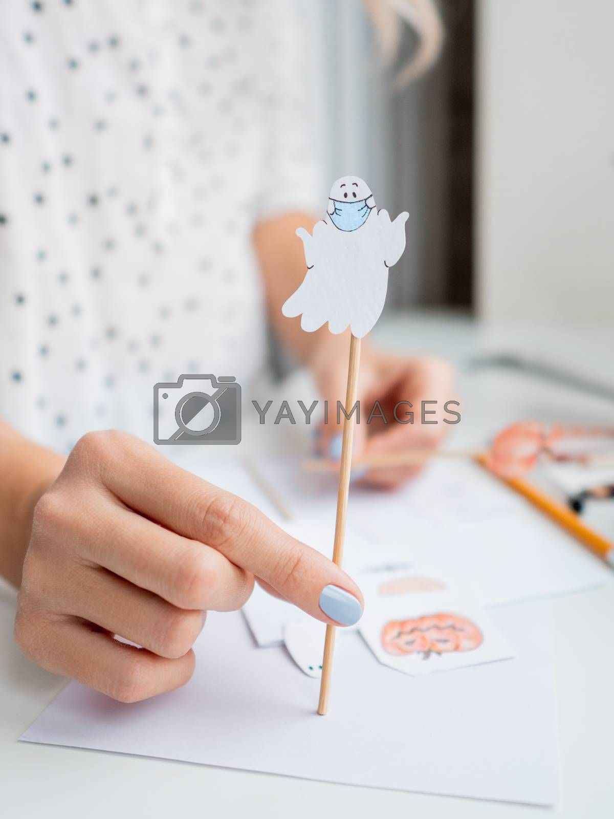 Woman with blue polish on nails paints ghost in medical protective mask. Handmade decorations for Halloween. DIY stickers on for flower pots. Socially-Distanced Halloween at home.