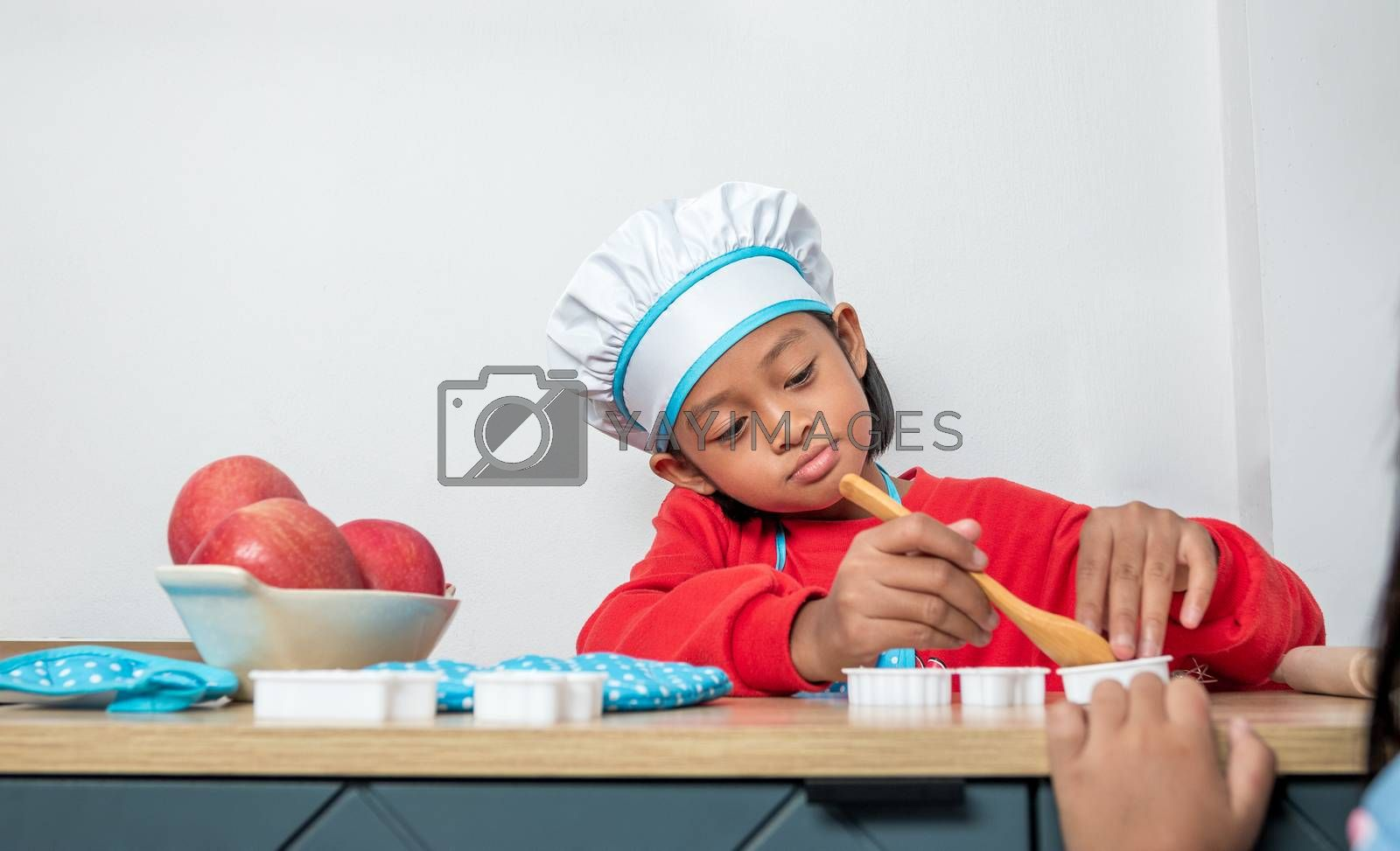 Cute girl in chef uniform and simulated cooking toys in the kitchen counter.