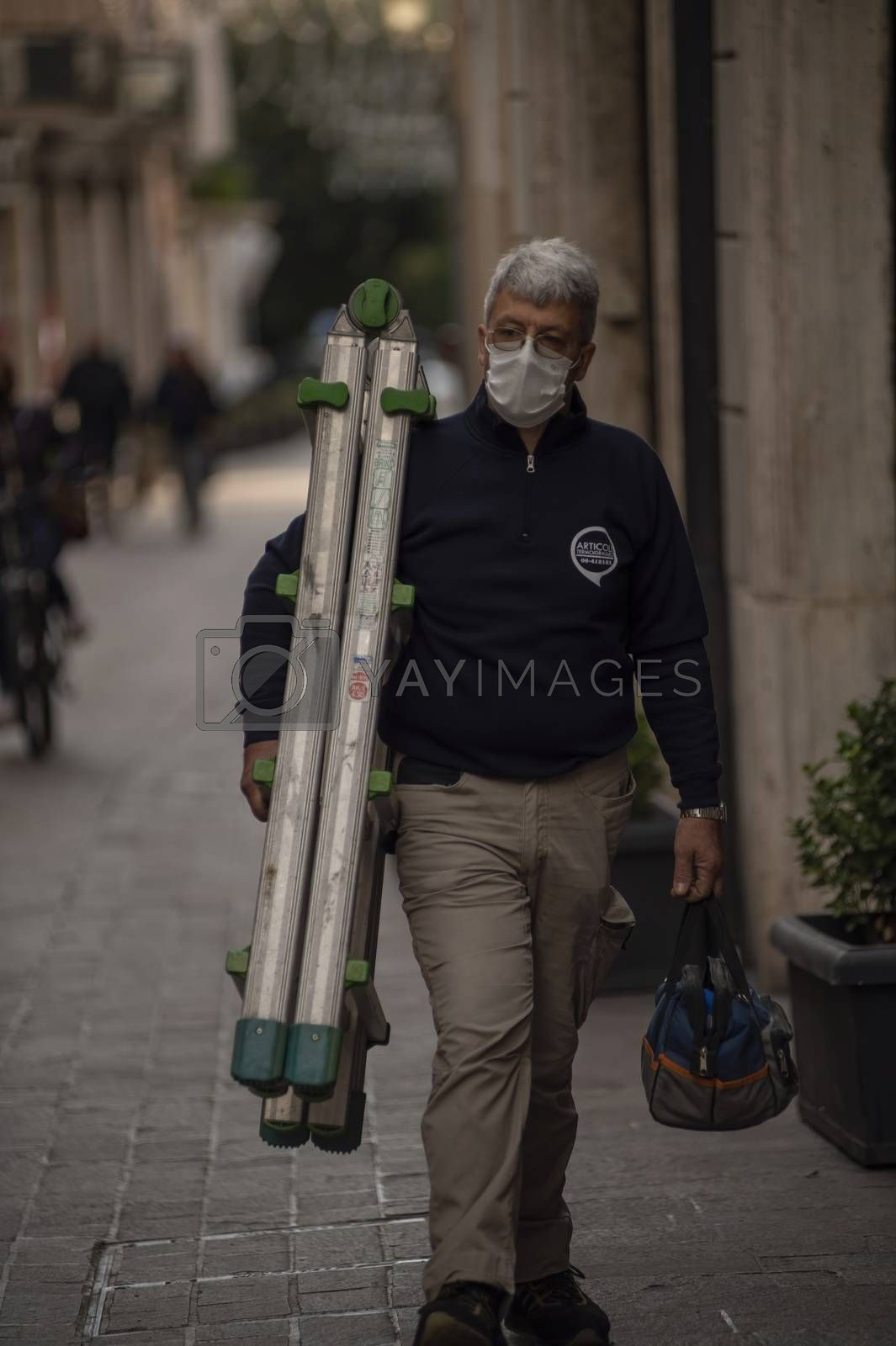 terni,italy october 26 2020:man with scale working wears medical mask cause covid 19