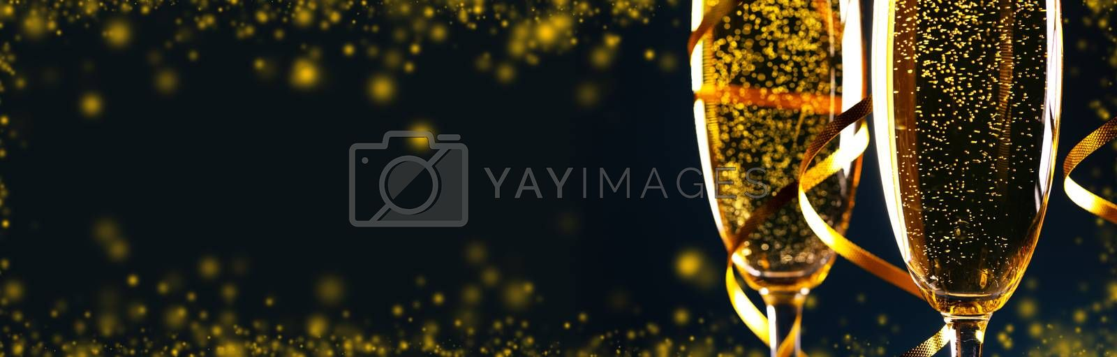 Champagne glasses with golden ribbon on black background with copy space - new year holiday celebration