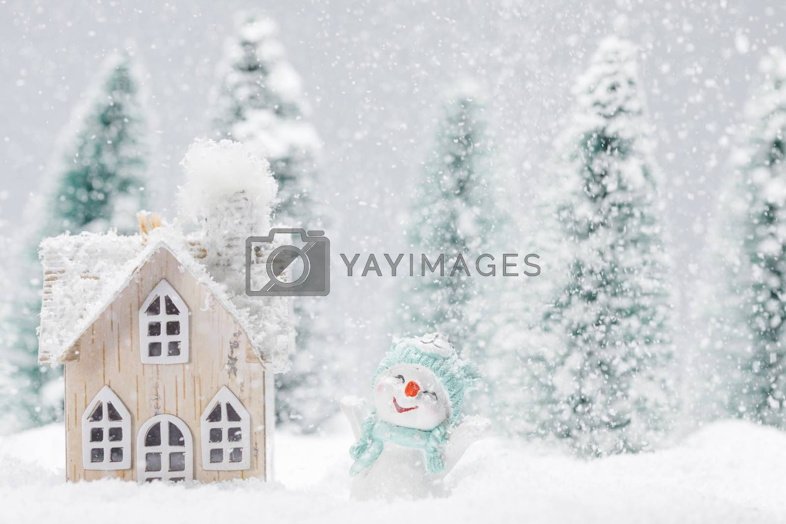 Small decorative snowman near wooden house in fir forest under falling snow