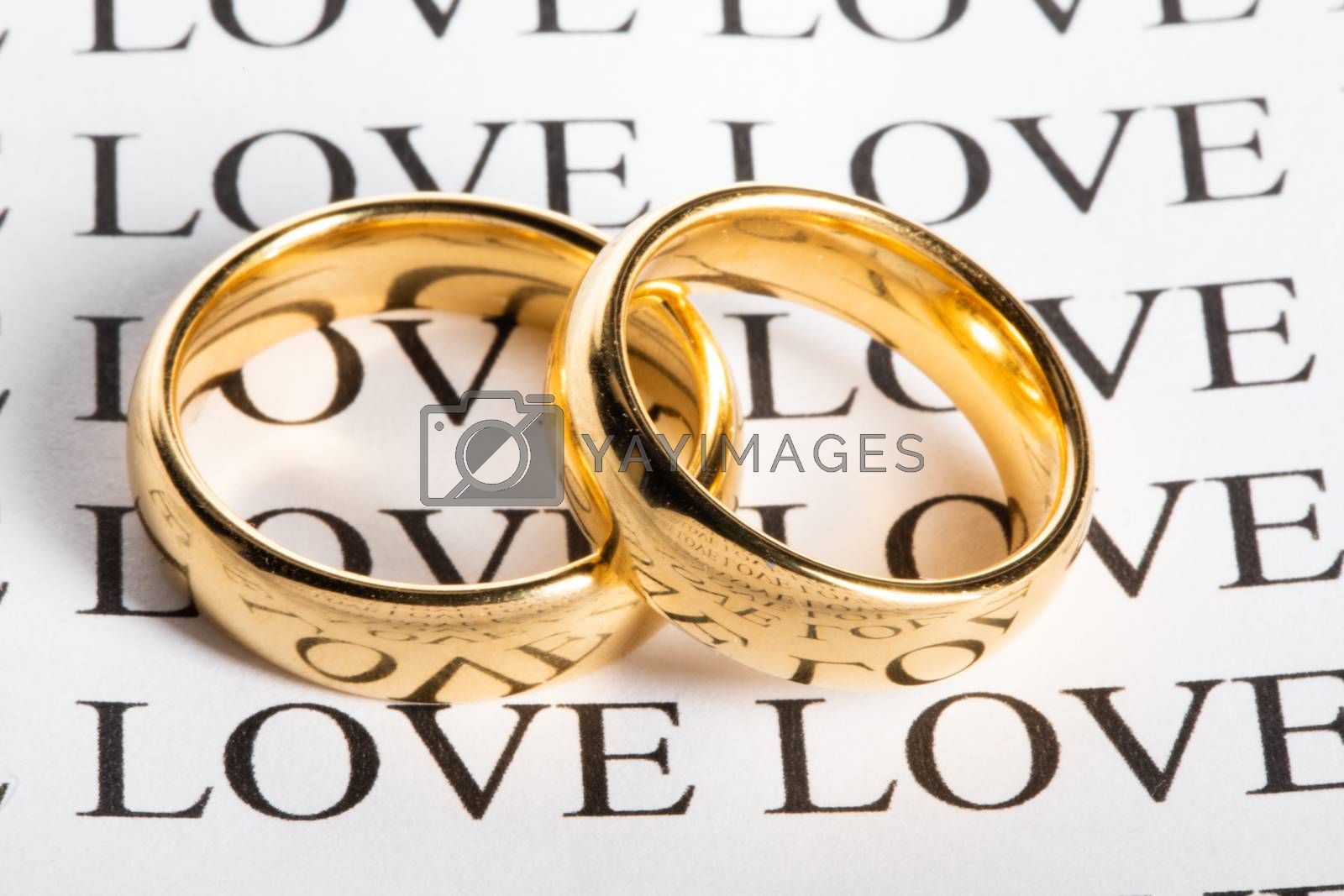 Two golden wedding rings with a word love close up