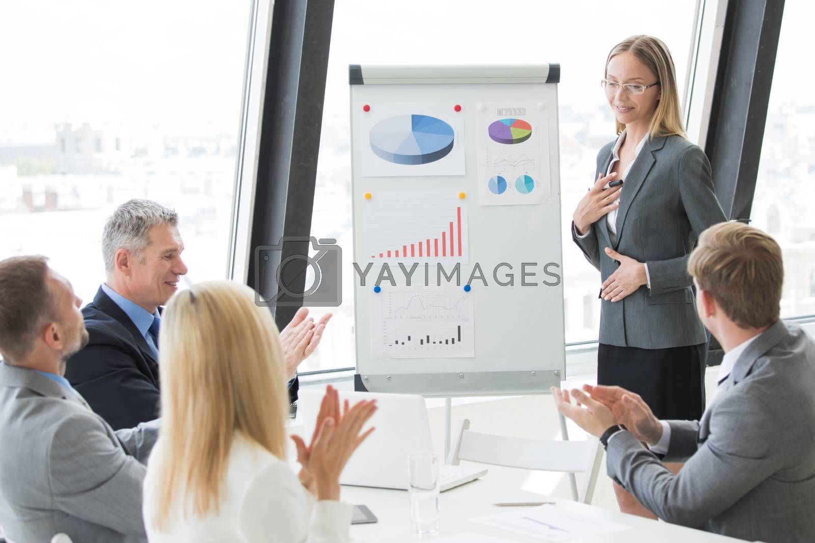 Businesswoman giving presentation using financial diagrams at flipchart to colleagues in office at meeting