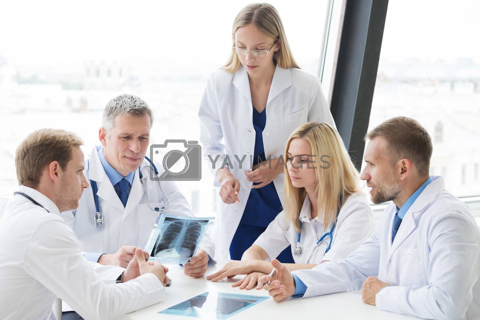 Team of experts doctors examining lungs X-ray report on hospital office meeting