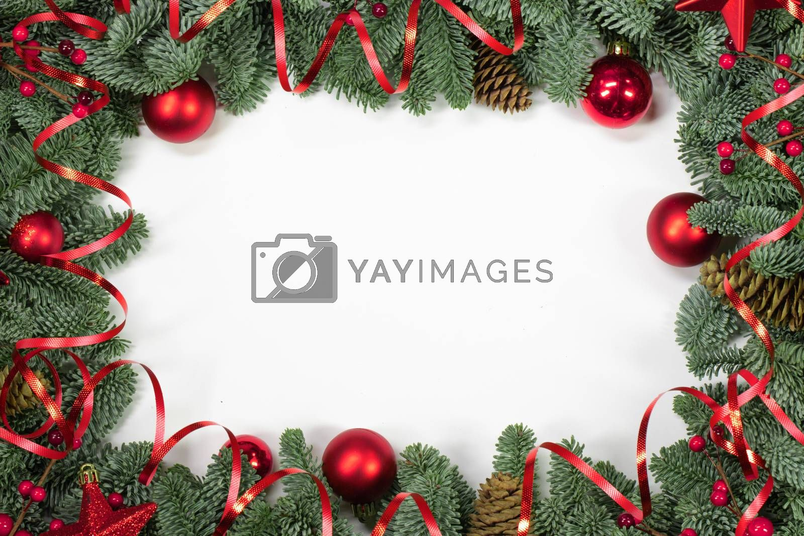 Christmas border frame design copmosition of noble fir tree branch and red decorations balls baubles pine cones isolated on white background