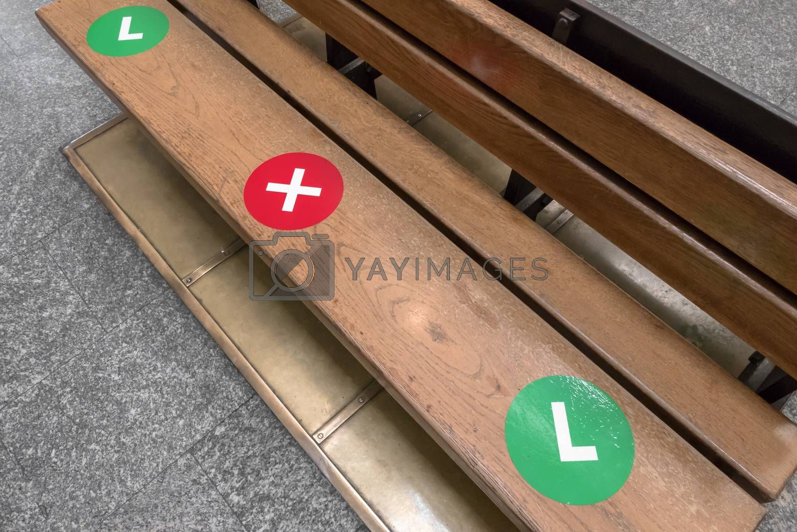The green dot stickers are being placed on wooden park chair to show people where they can sit while maintaining social distancing. The red color to show people where don't sit. Safety for pandemic covid.