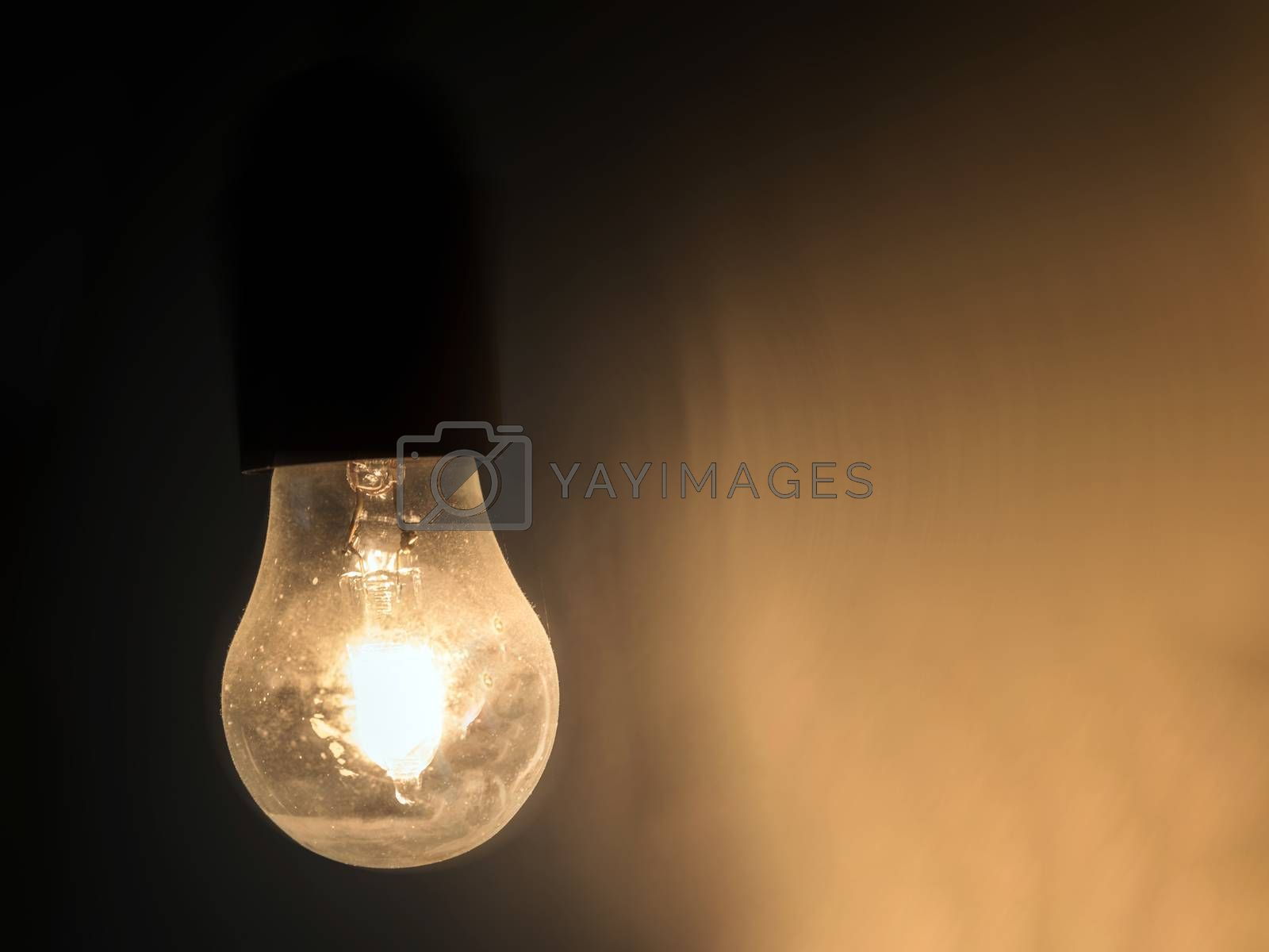 Vintage light bulb glowing in the dark. Ideal for concepts.