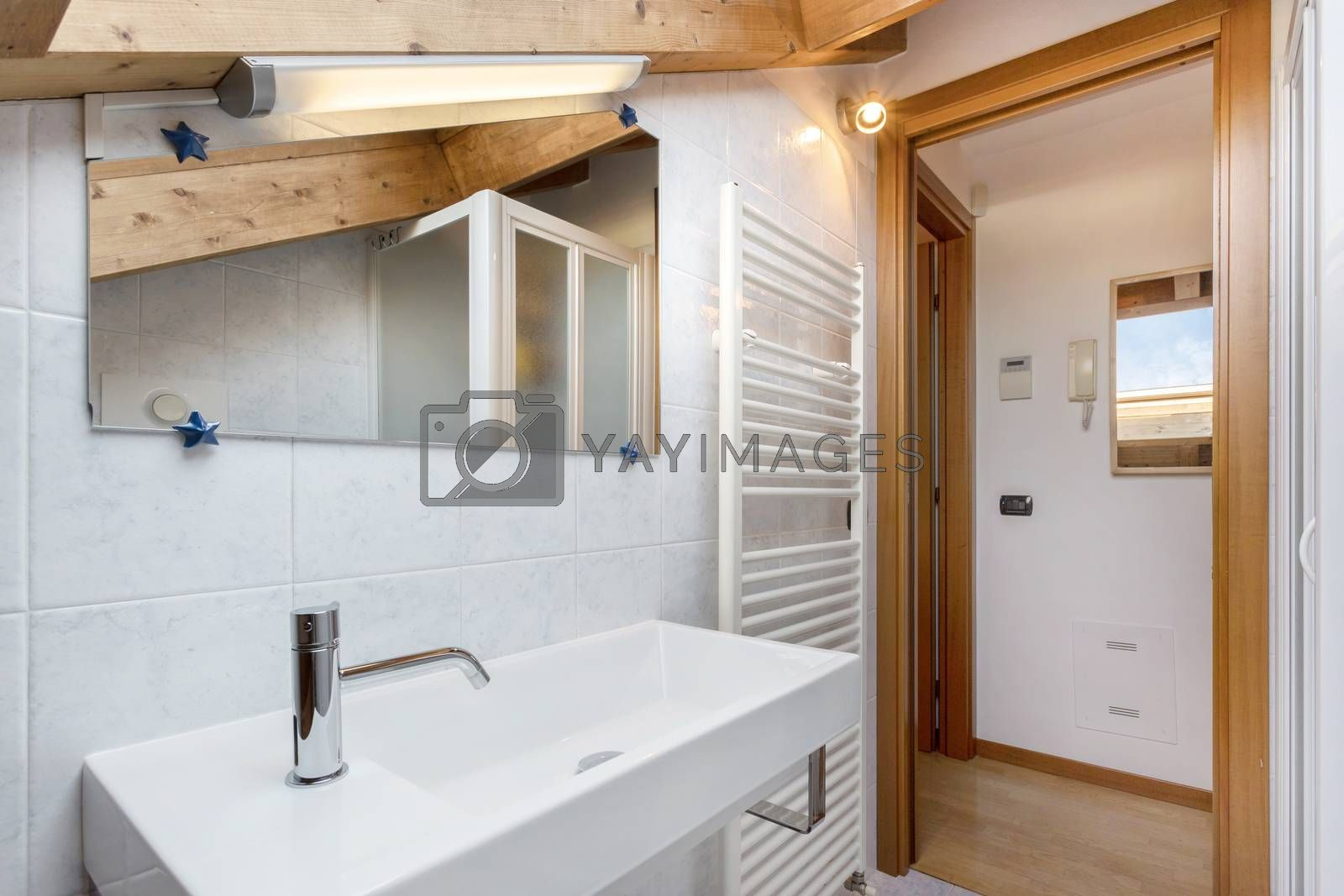 Practical and cozy bathroom with towel radiator, toilet, cabinet and sink. Roof with exposed wooden beams. Classical italian design and style.