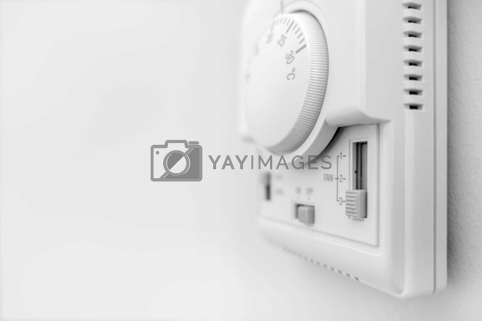 Hand adjusting thermostat. hand turning on thermostat climate control. Copy space. Defocused blurry background.