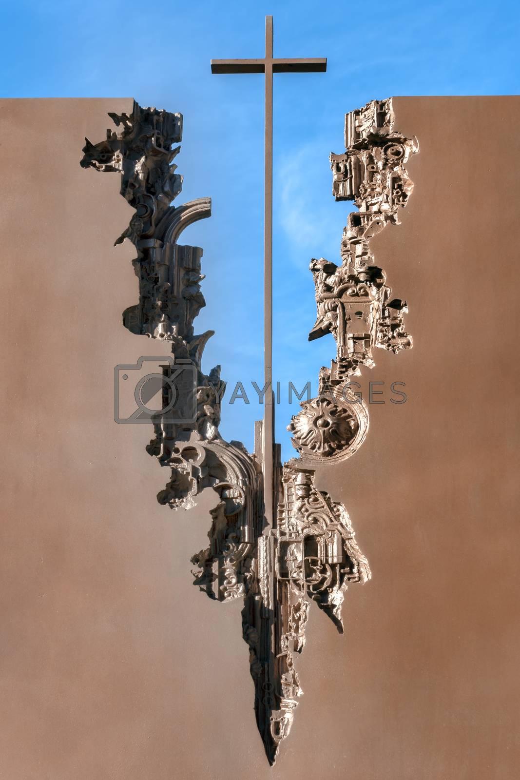 Modern sculpture of an iron cross with gears.