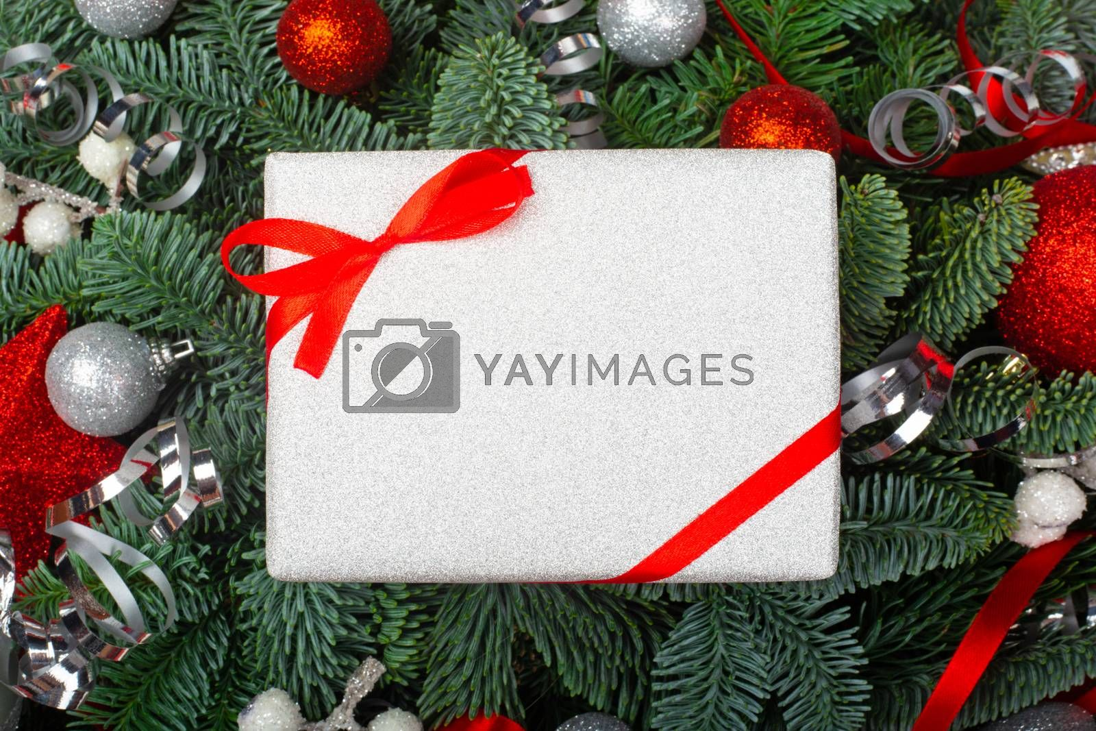 Christmas noble fir tree branches gift and red baubles background with copy space for text