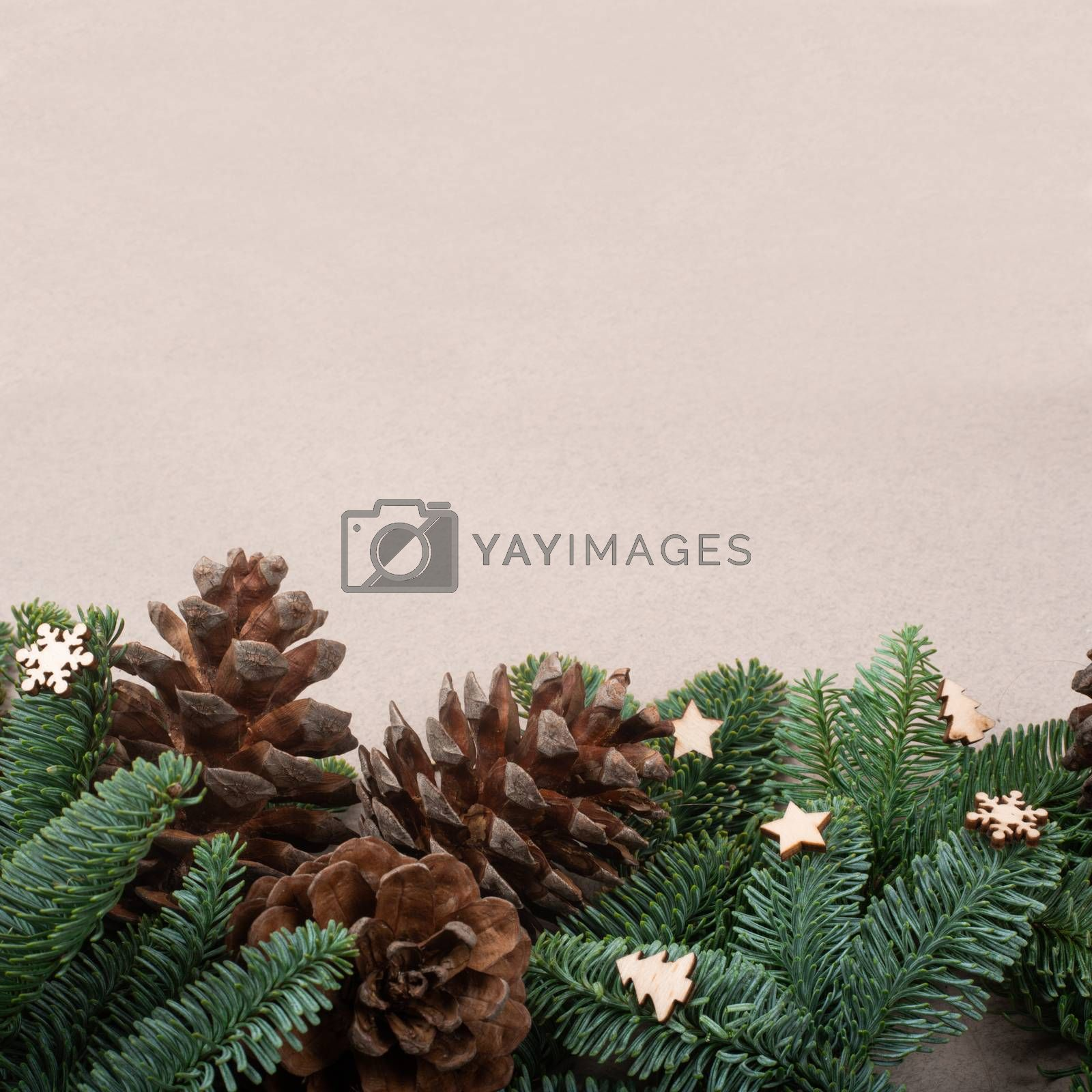 Christmas card light background with wooden decor fir tree branches border frame with copy space