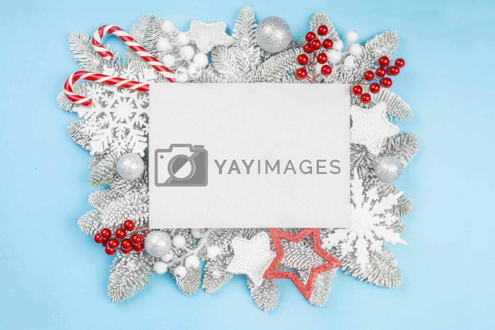 Frosted fir tree twigs and Christmas decorative bauble balls on blue background with white rectangle card with copy space for text template flat lay top view design