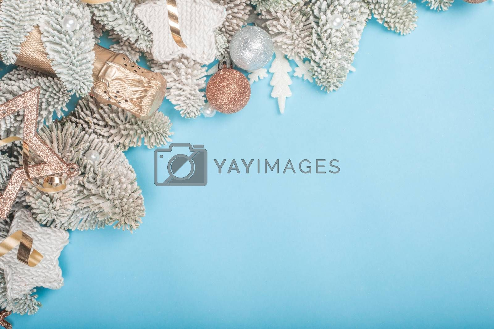 Frosted fir tree twigs and Christmas decorative bauble balls on blue background with copy space for text template flat lay top view design