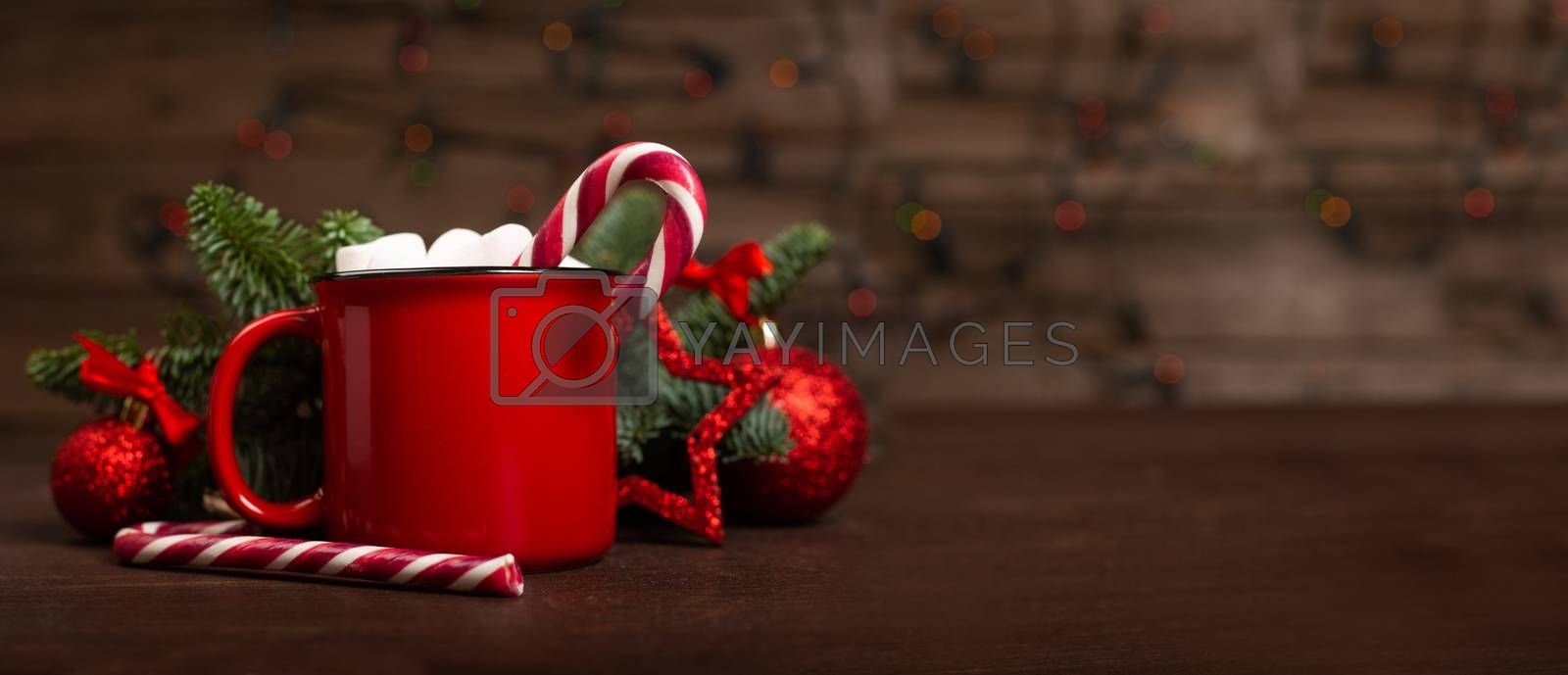 Cocoa hot chocolate in red mug with marshmallows candy cane fir tree branches and red baubles on dark wooden background