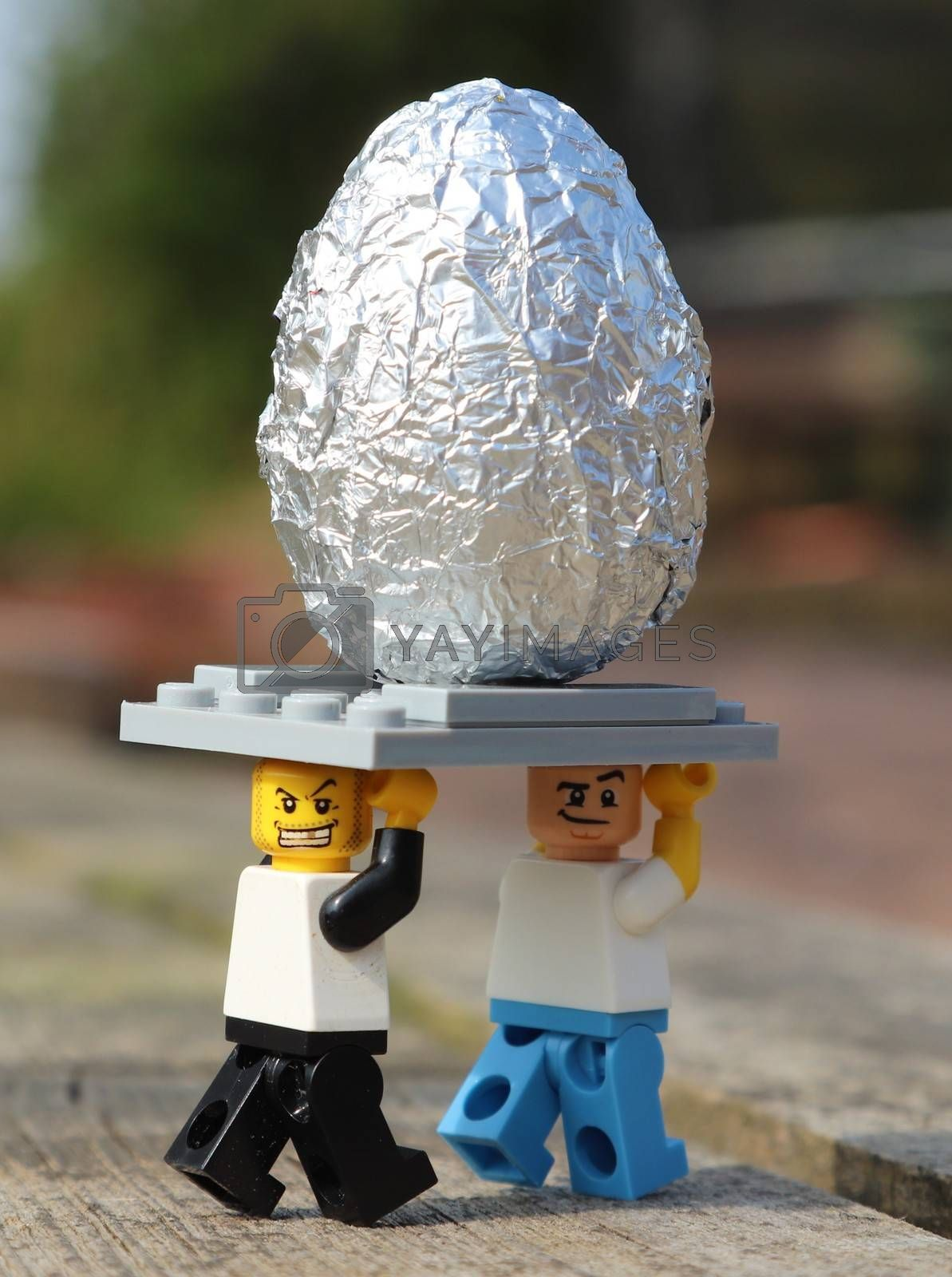Two Lego people carrying away a silver Easter egg outside in sunshine