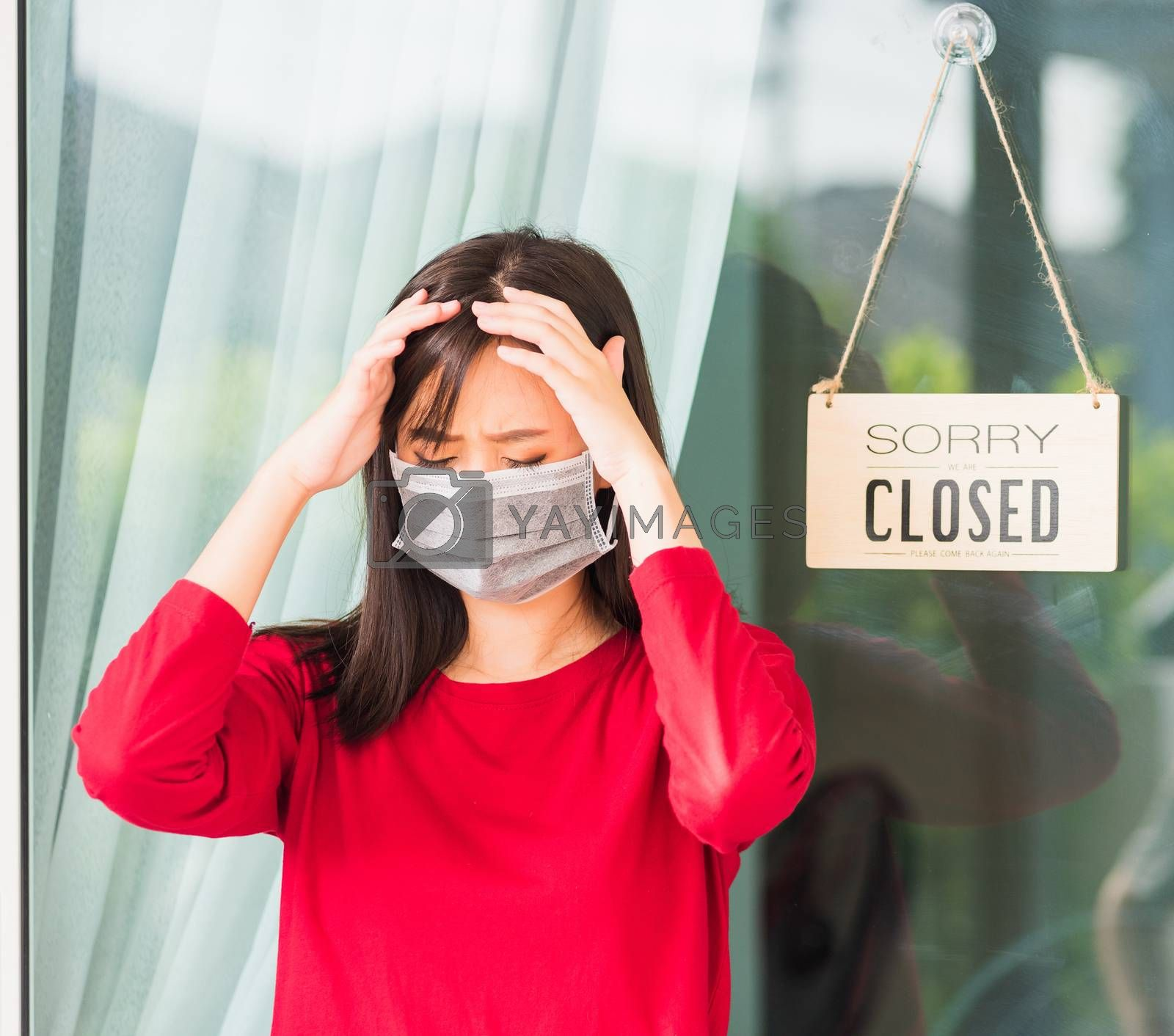 """Asian young woman wear face mask protect she sad notice sign wood board label """"SORRY WE ARE CLOSED PLEASE COME BACK AGAIN"""" hanging through glass door front business shop, coronavirus pandemic disease"""