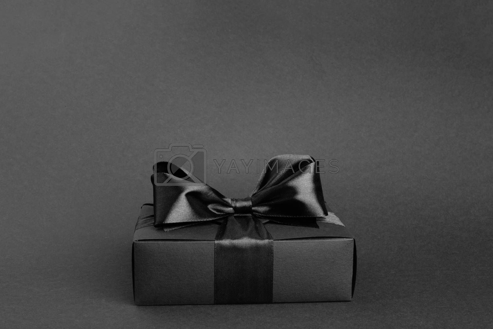 Black friday gift, paper box with silk ribbon bow on black background