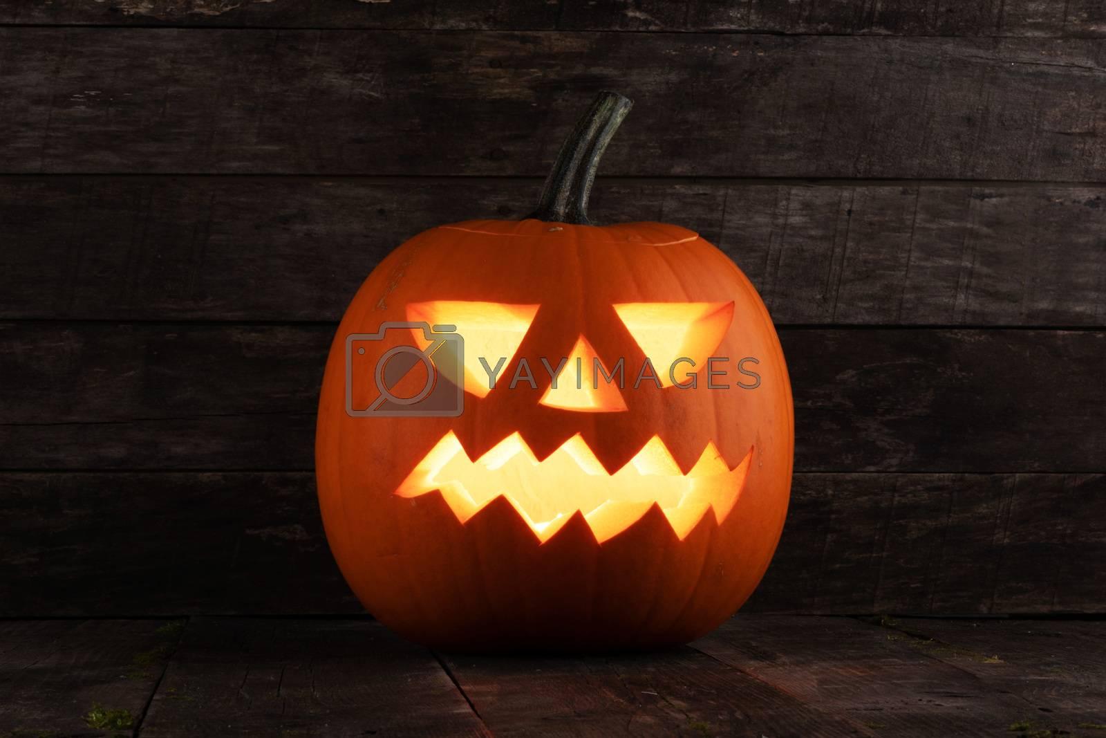 Carved jack-o-lantern halloween pumpkin on wooden background