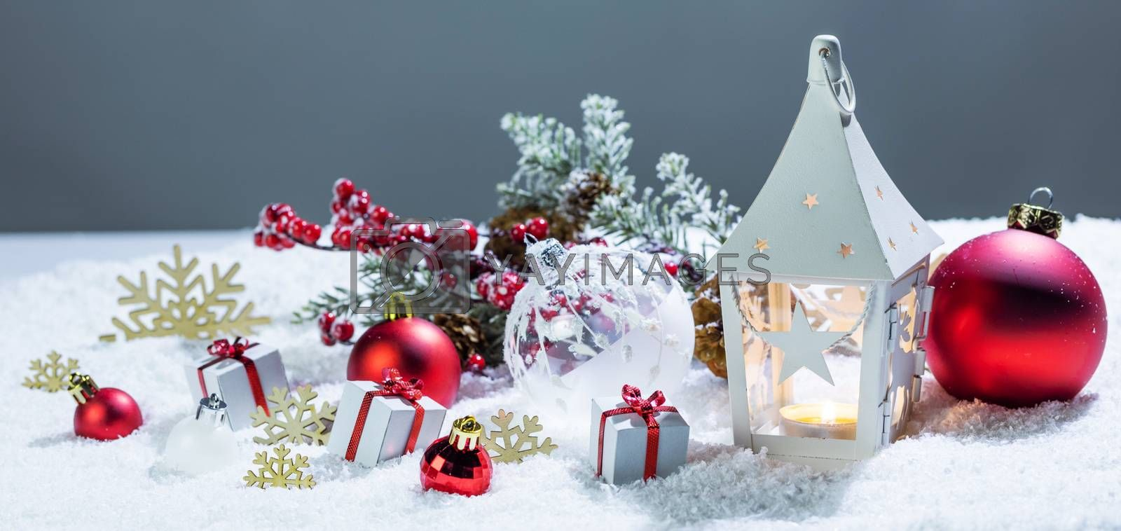 Christmas holidays card with gifts , balls , and white glowing lantern in snow