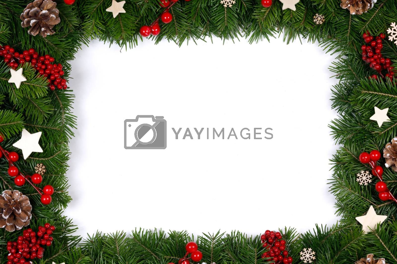 Christmas Border frame of tree branches on white background with copy space isolated, red and white decor, berries, stars, cones