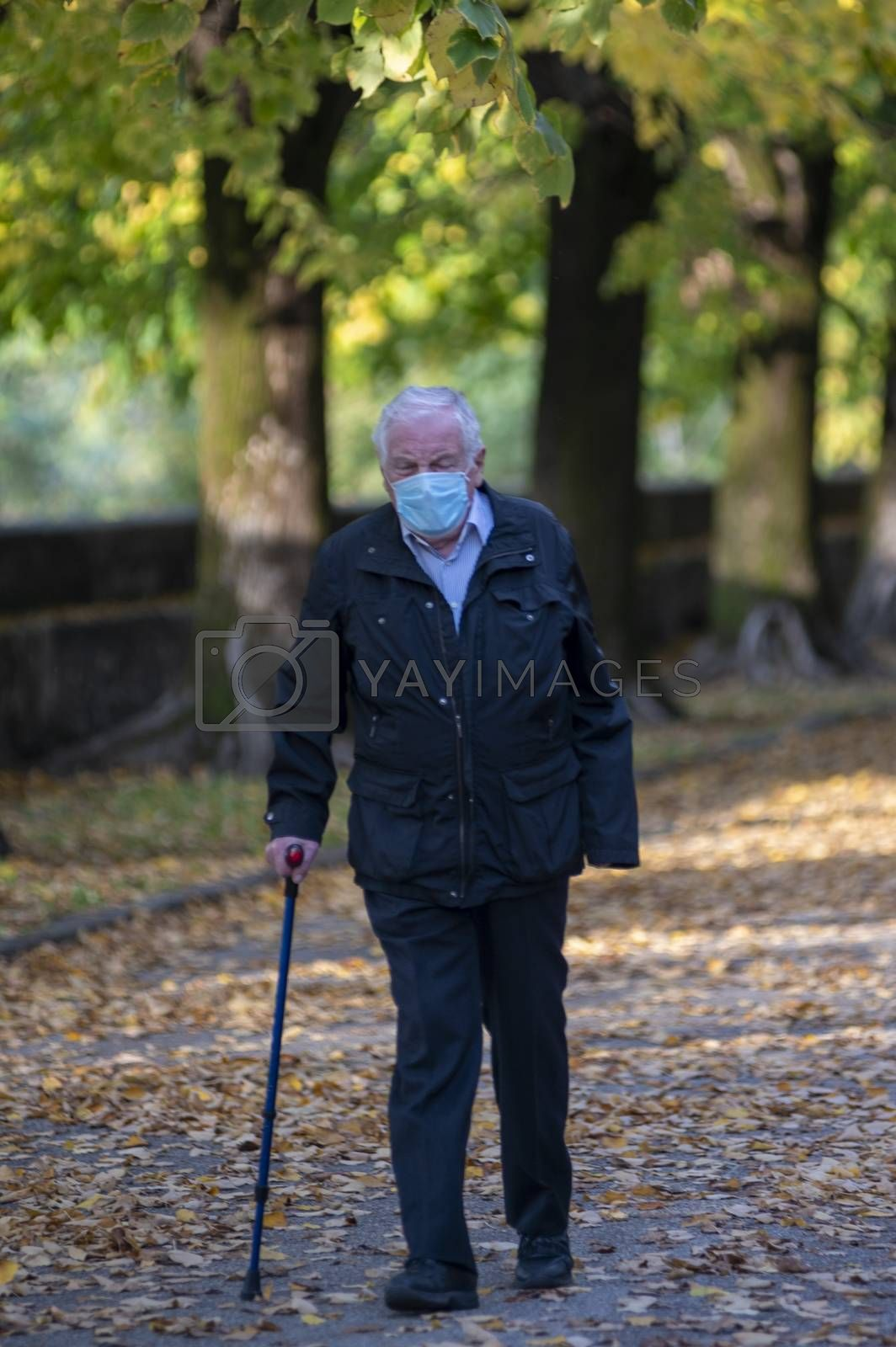 terni,italy october 27 2020:anxious man walking with cane and wearing medical mask