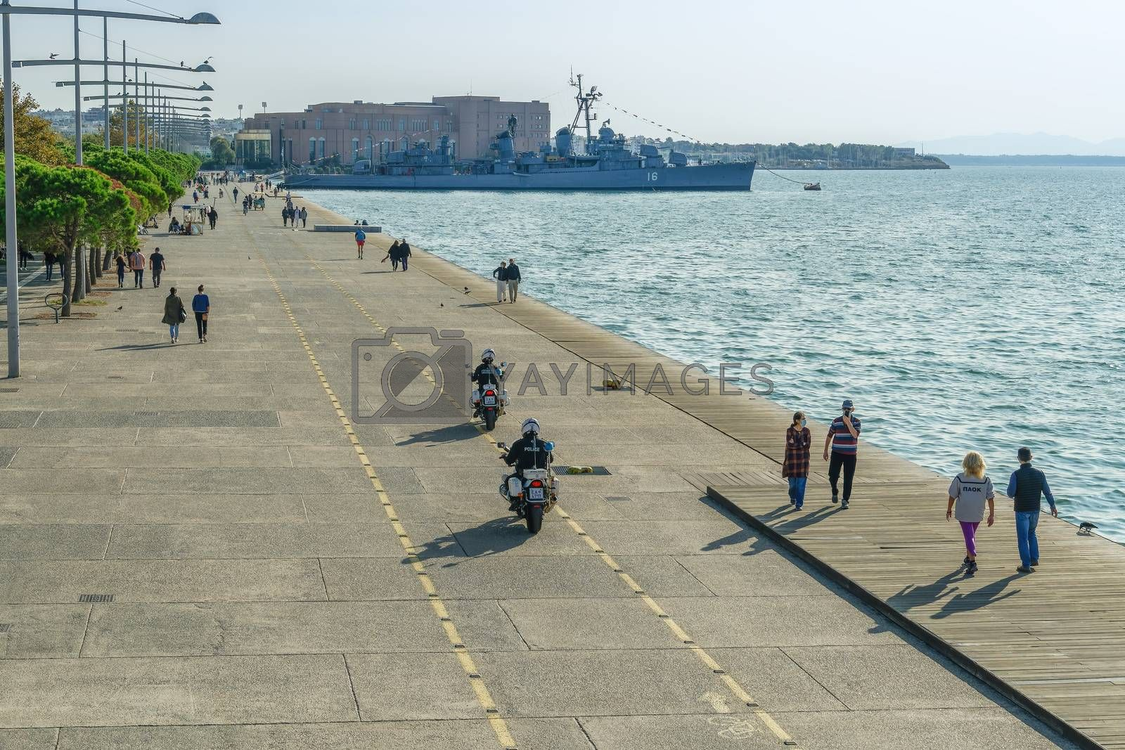 Unidentified persons with face protection walk on the pedestrian area of the city waterfront in Thessaloniki, Greece.