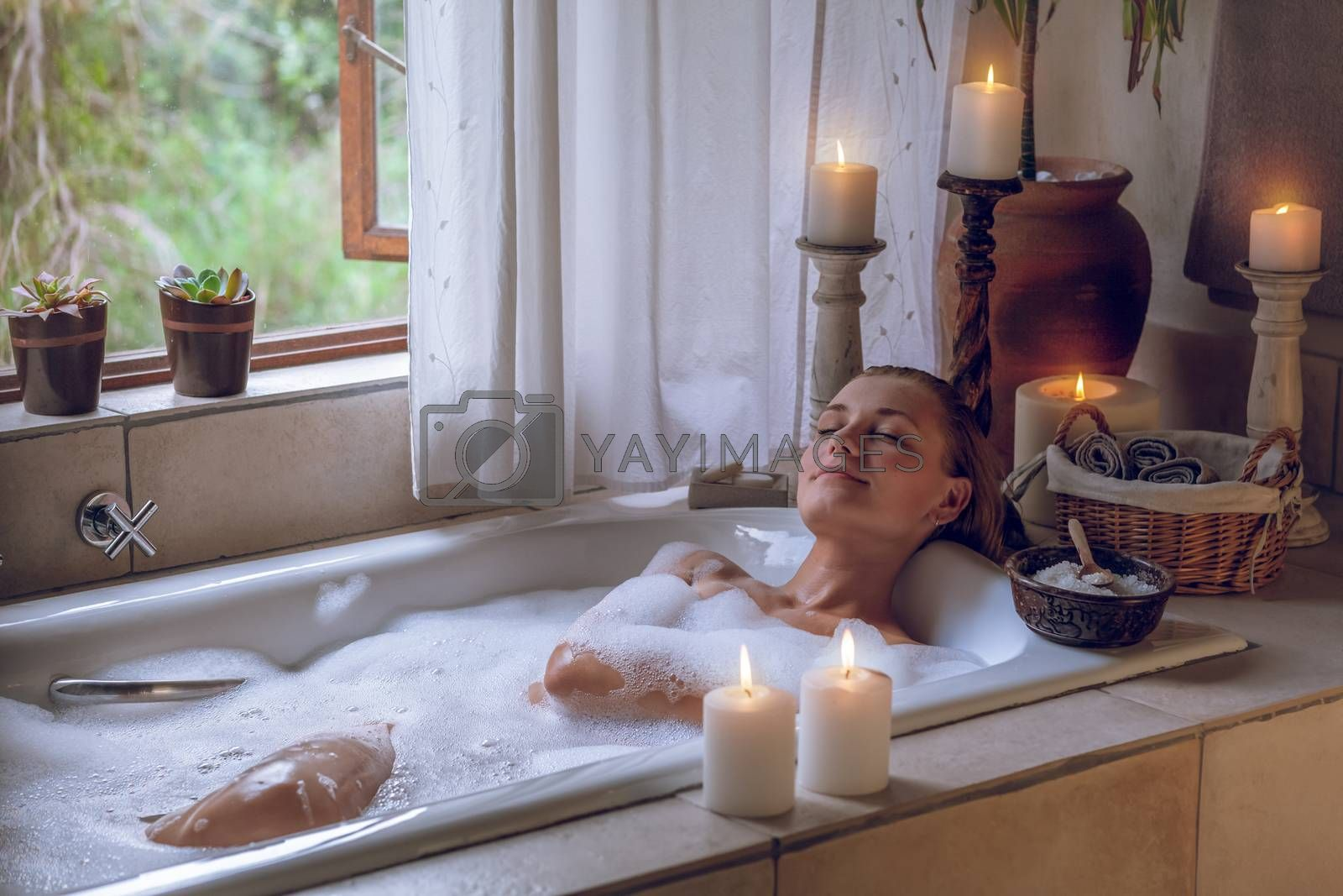 Beautiful Woman with Pleasure Lying Down in the Bath With Foam. Enjoying Weekend at Spa Hotel. Pampering Day.