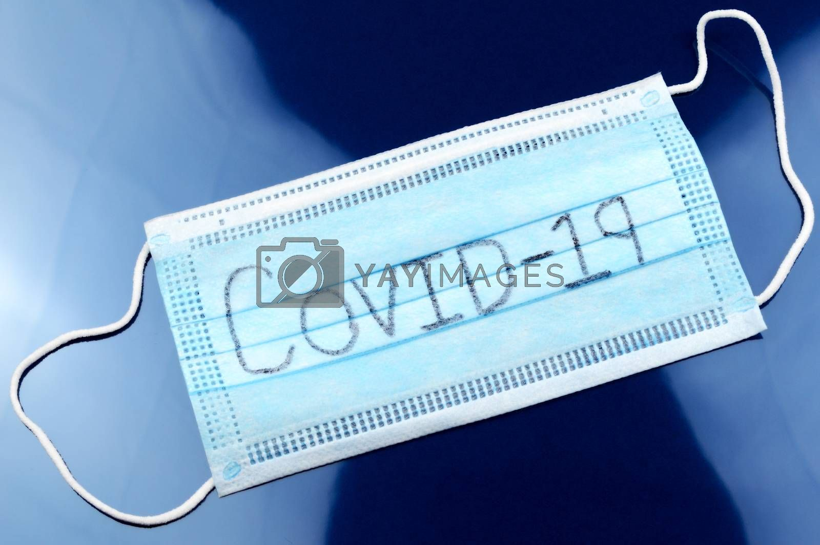 A face mask with the handwritten word Covid-19 for the global Coronavirus outbreak starting in 2019.