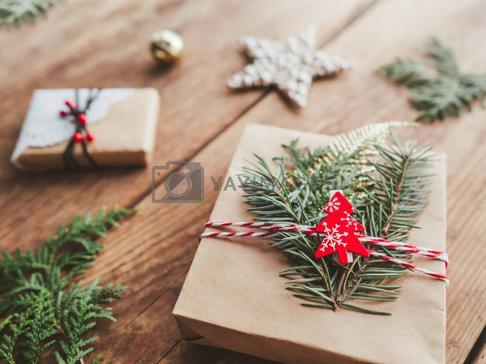 Christmas DIY presents wrapped in craft paper with fir tree twigs. Red decorations in shape of Christmas tree, stars. New Year gifts on wooden background. Winter holiday spirit.