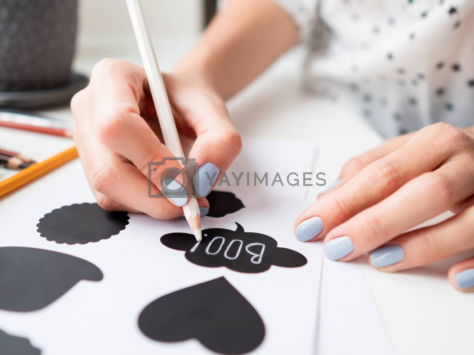 Woman writes Boo! on decorative black stickers for flower pots. Handmade decorations for Halloween.