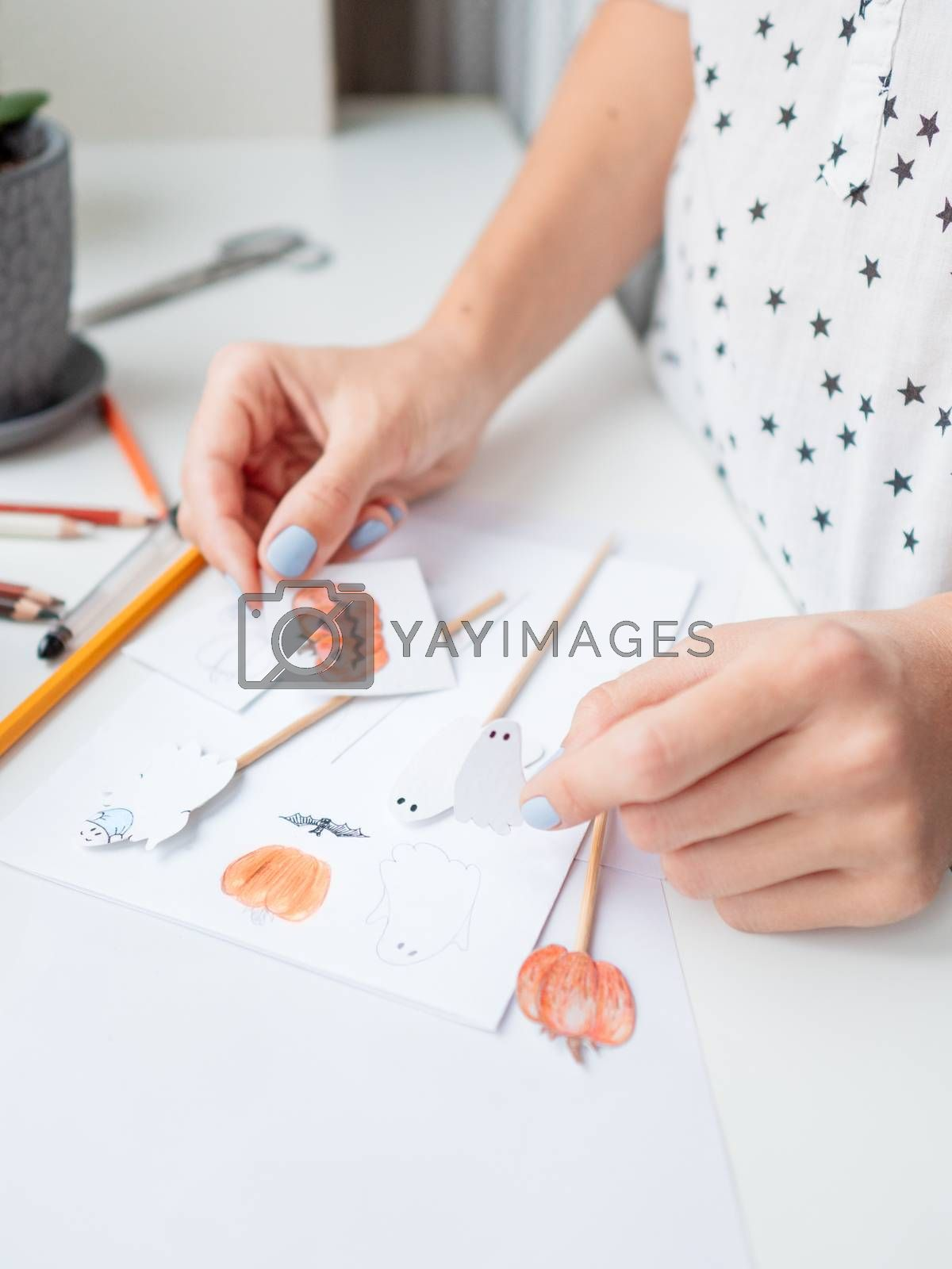 Woman draws pumpkins and ghosts in medical protective mask. Handmade decorations for Halloween 2020. DIY stickers on for flower pots. Socially-Distanced Halloween at home.