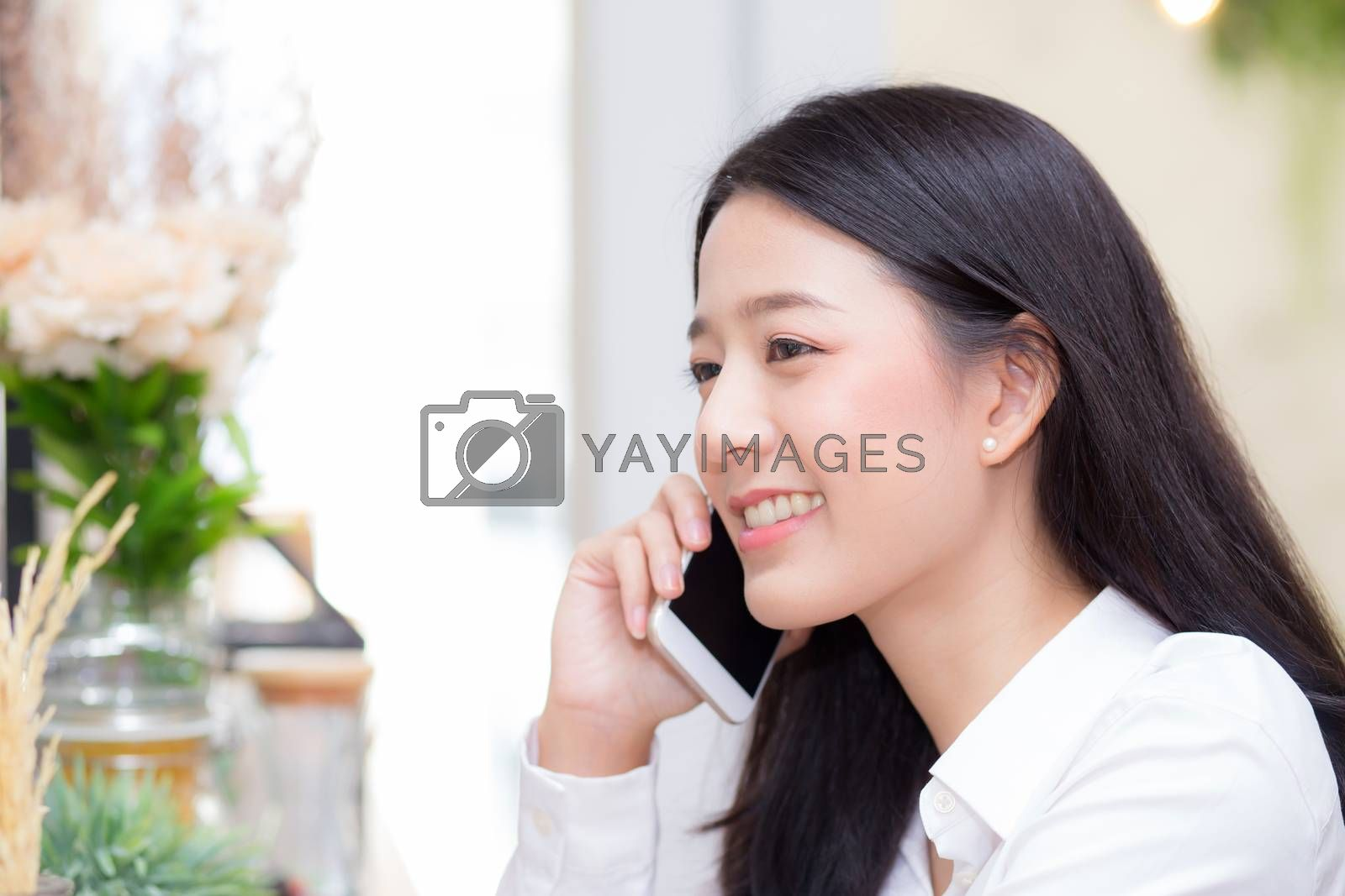 Beautiful young asian woman talking phone and smile in the coffe by nnudoo