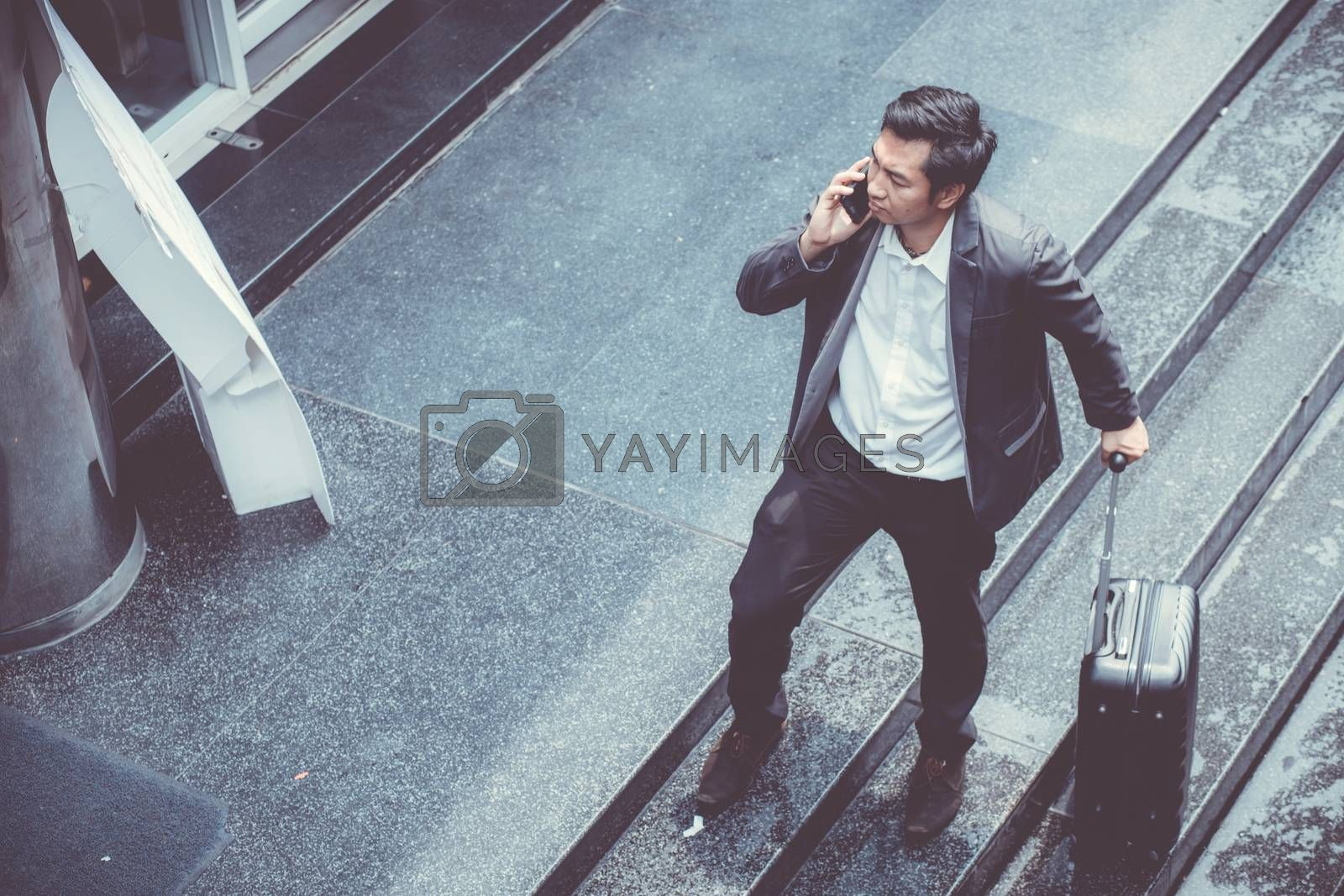 Asian elegant businessman wear suit talking mobile phone while walking holding suitcase outdoor on street, young man contact with customer appointment, communication business concept.