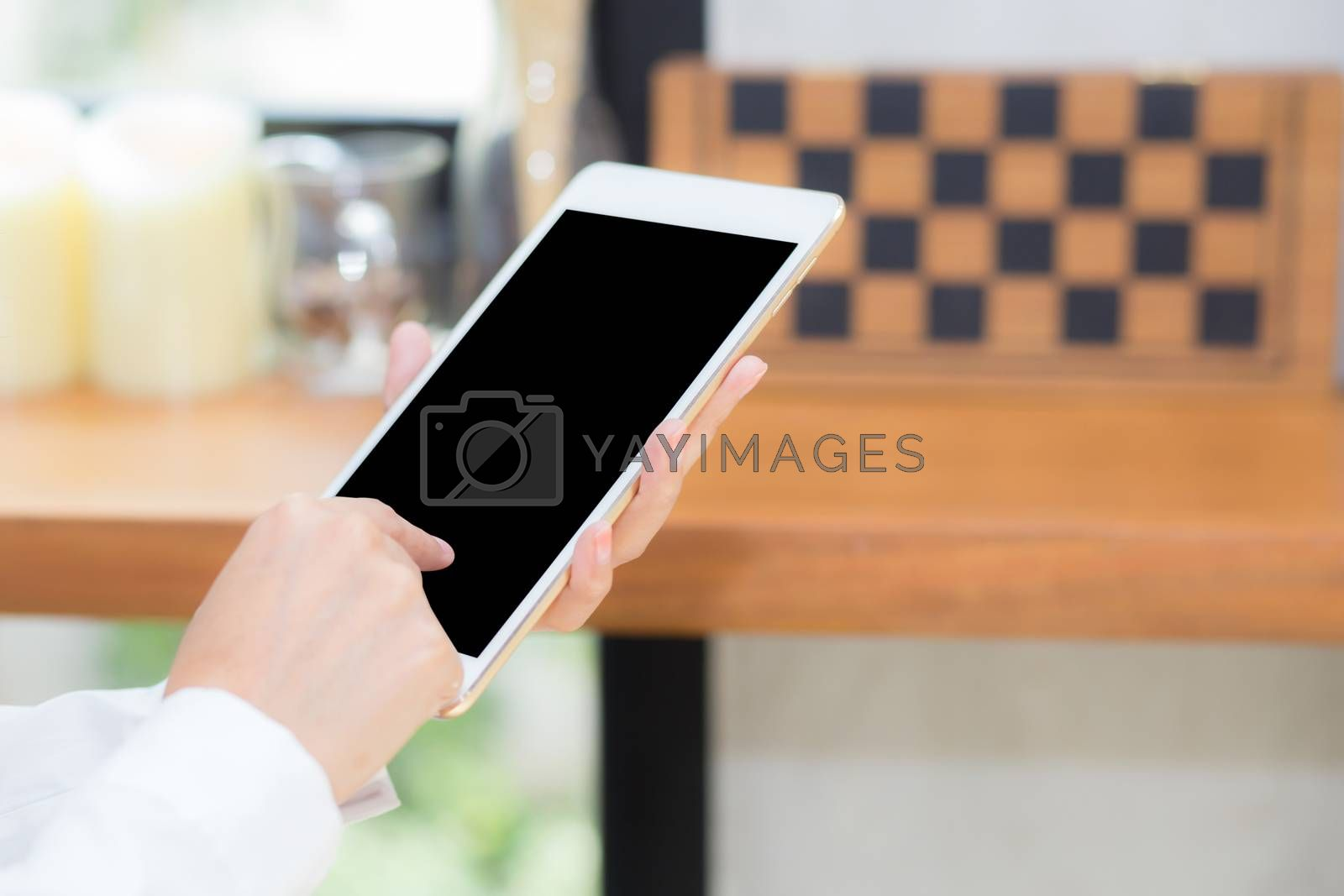 Closeup woman using tablet computer in the coffee shop, businesswoman sitting looking tablet is work at cafe, communication concept.