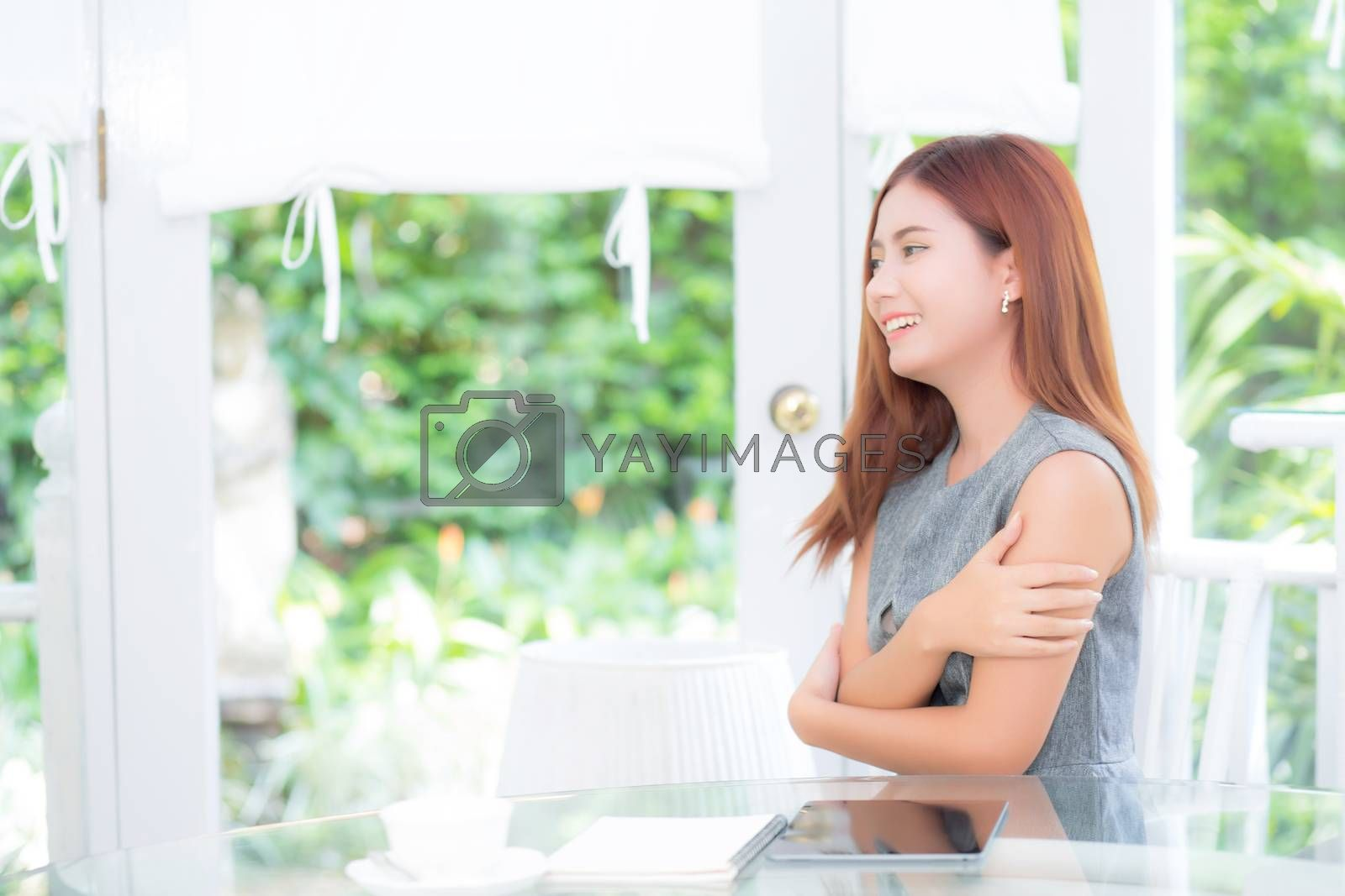 Beautiful of portrait businesswoman have enjoy in the garden with tablet and book, woman relax sitting in the park with smile and happy, communication and lifestyle concept.