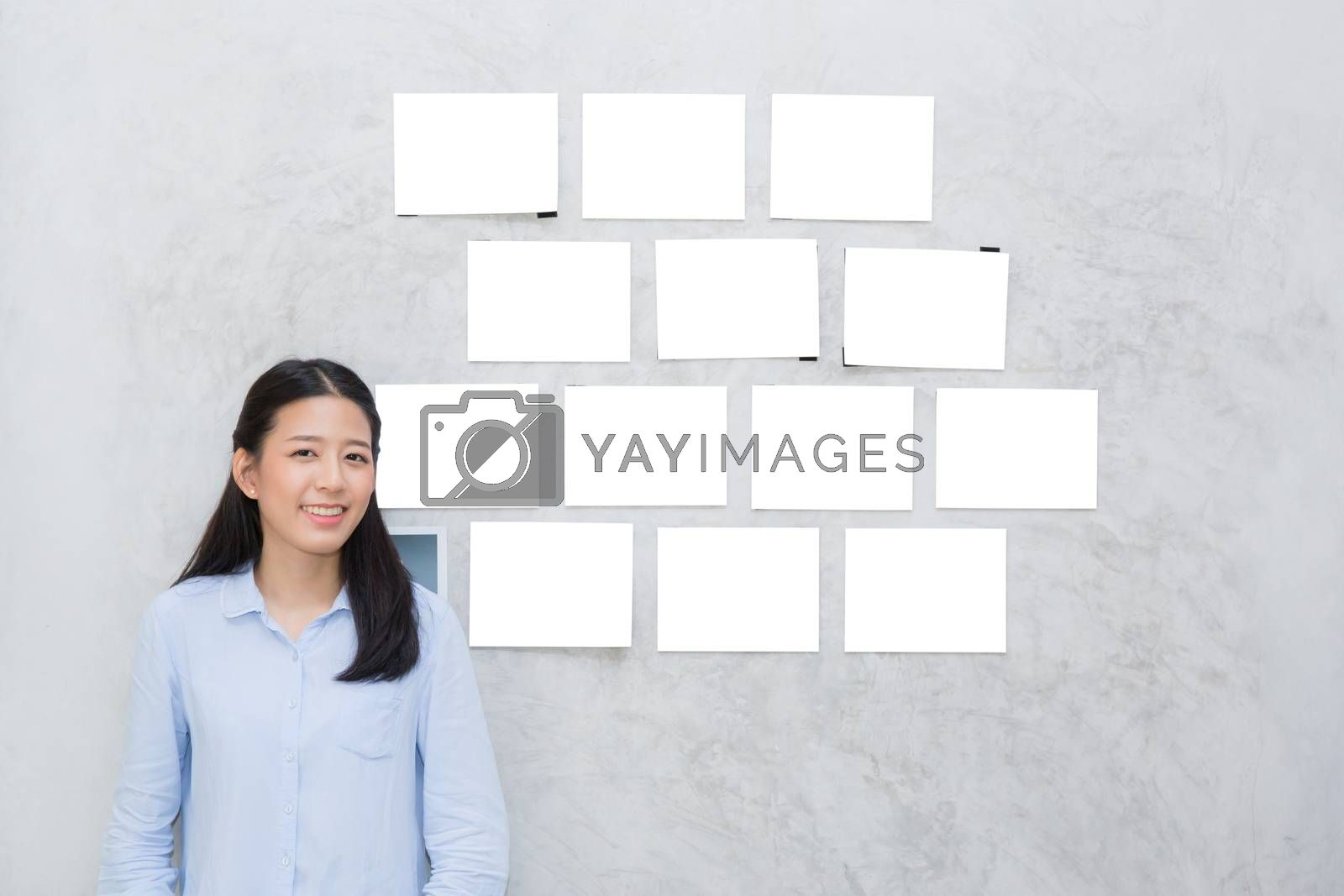 Beautiful of portrait asian young woman standing with picture gallery copy space on wall texture cement background.