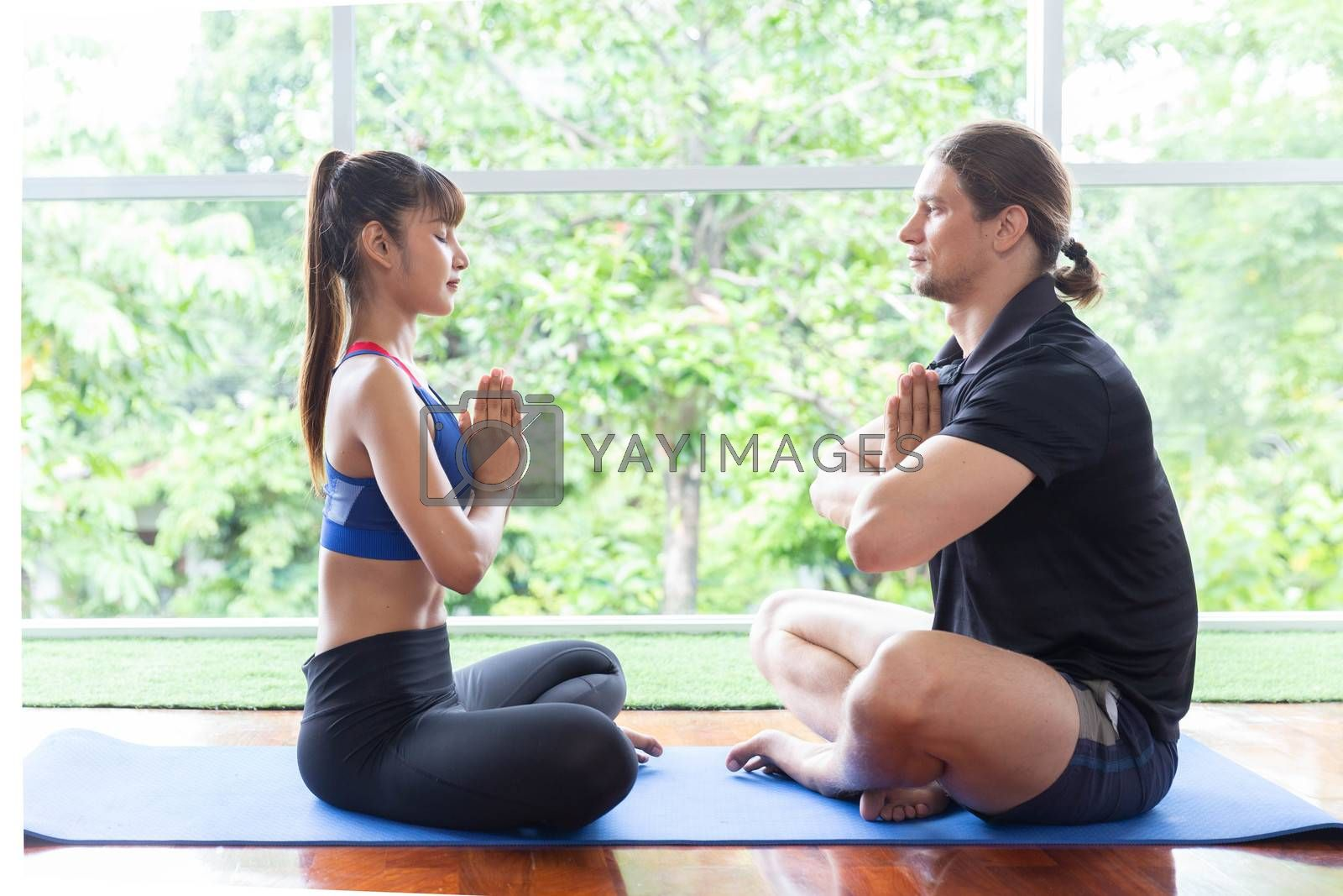 A couple in sport clothes is meditating sitting in lotus position on mat while doing yoga in living room at home