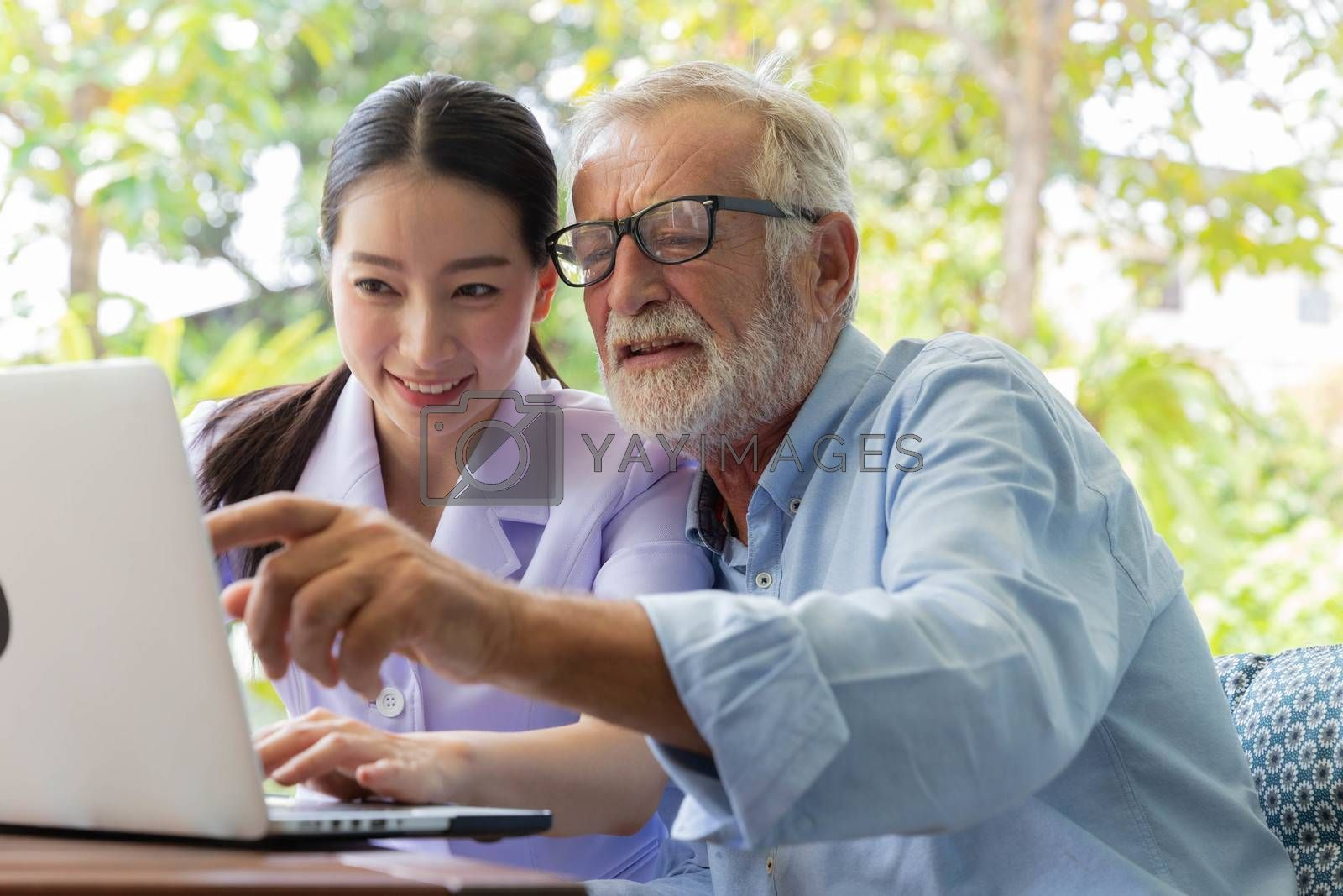 Nurse help senior retirement man working with laptop in the garden at home and feeling excited