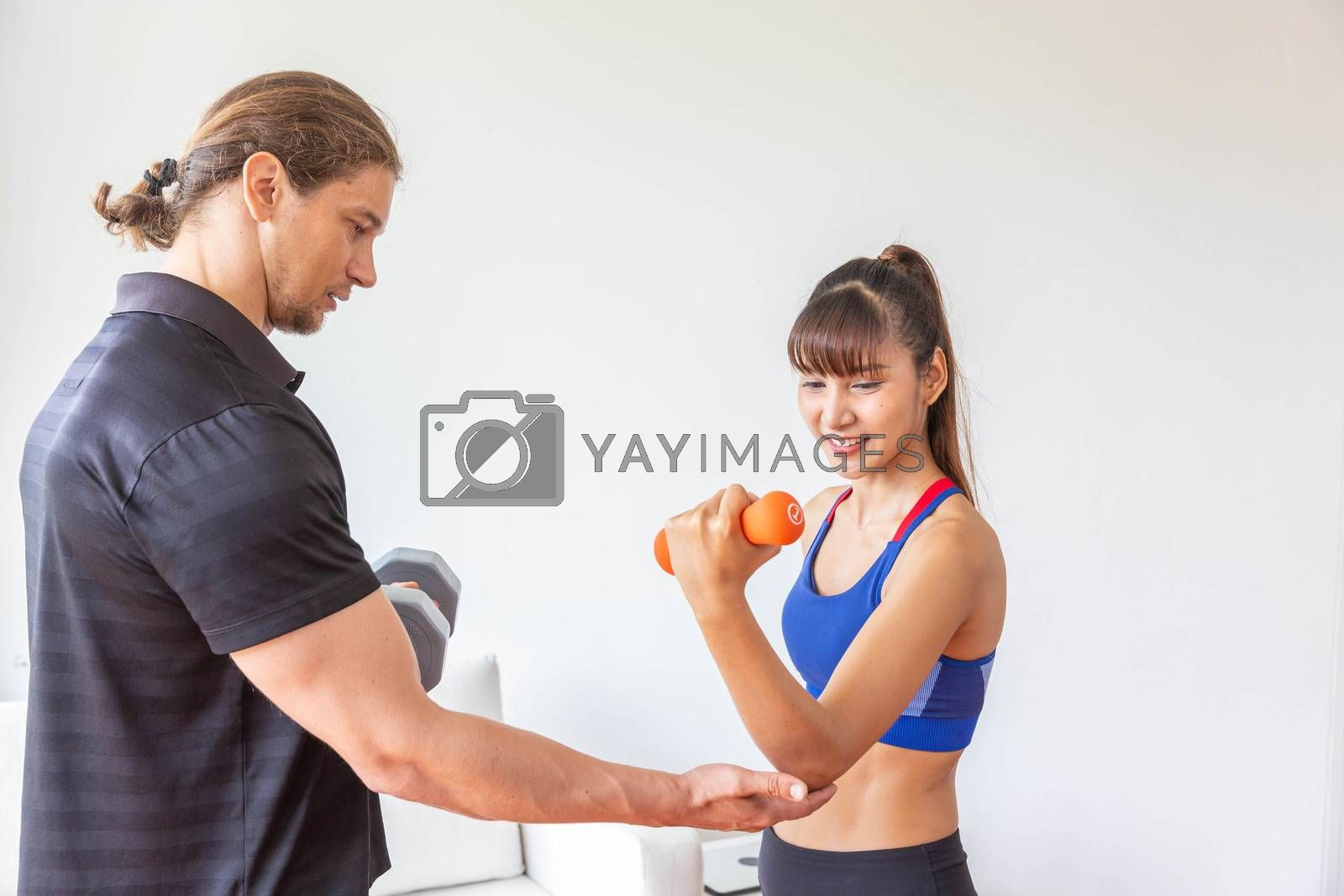 Sporty girl having weight exercise with assistance from her personal trainer at home