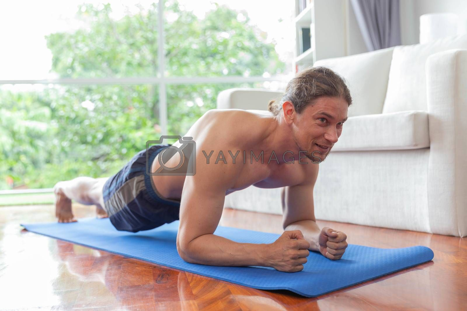 Smiling caucasian man plank exercise in living room at home