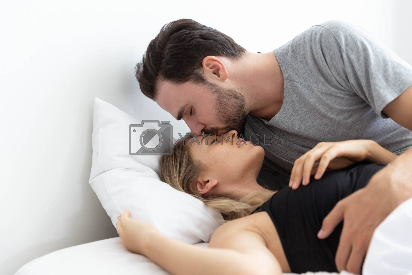 Caucasion couple on bed and man kiss women on her forehead