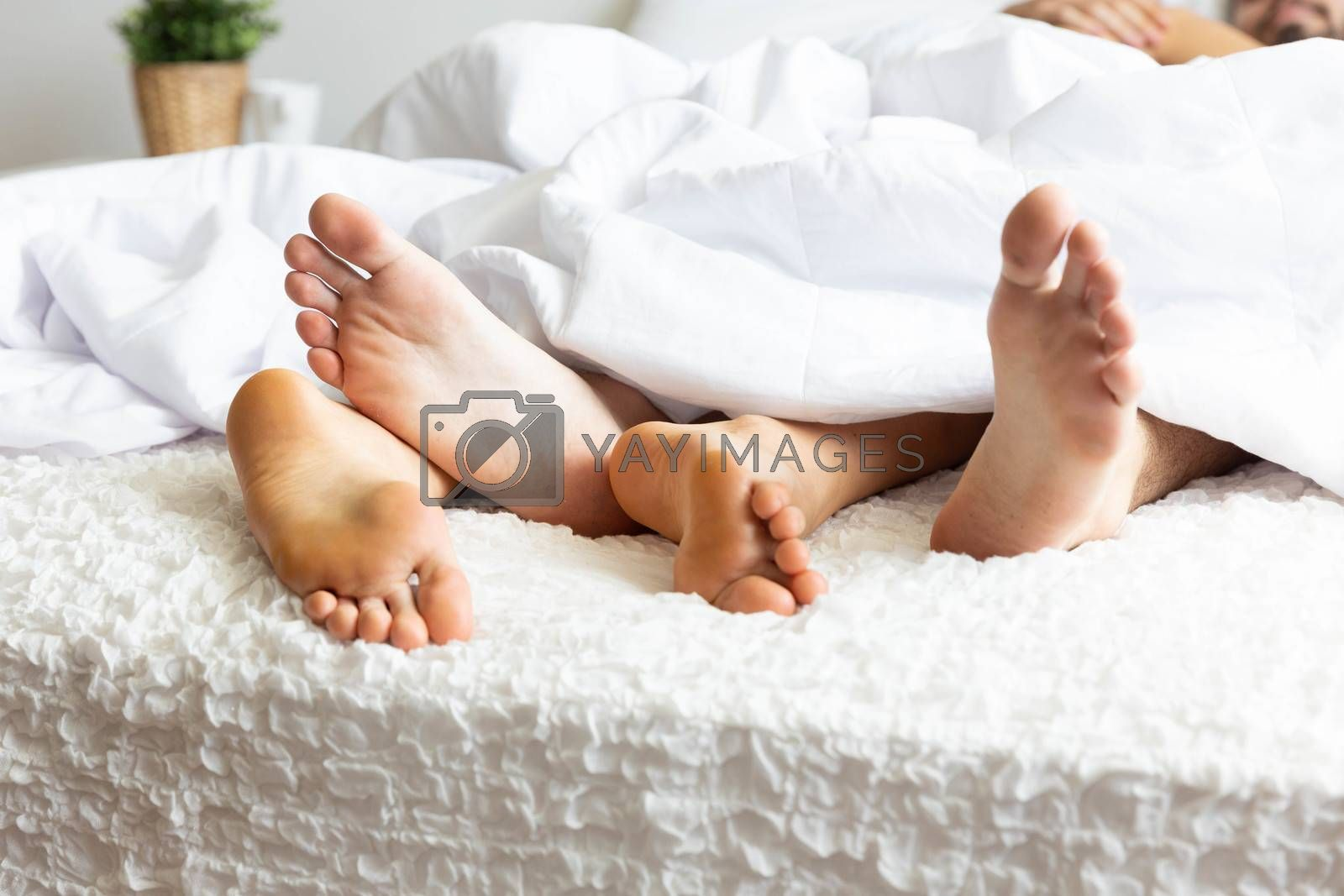 Feet of couple on bed and cross