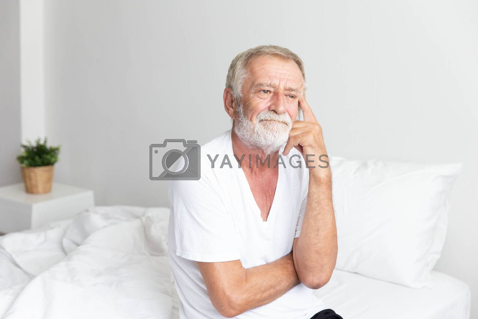 Portrait of a senior retirement man sitting and thinking alone on bed in his home