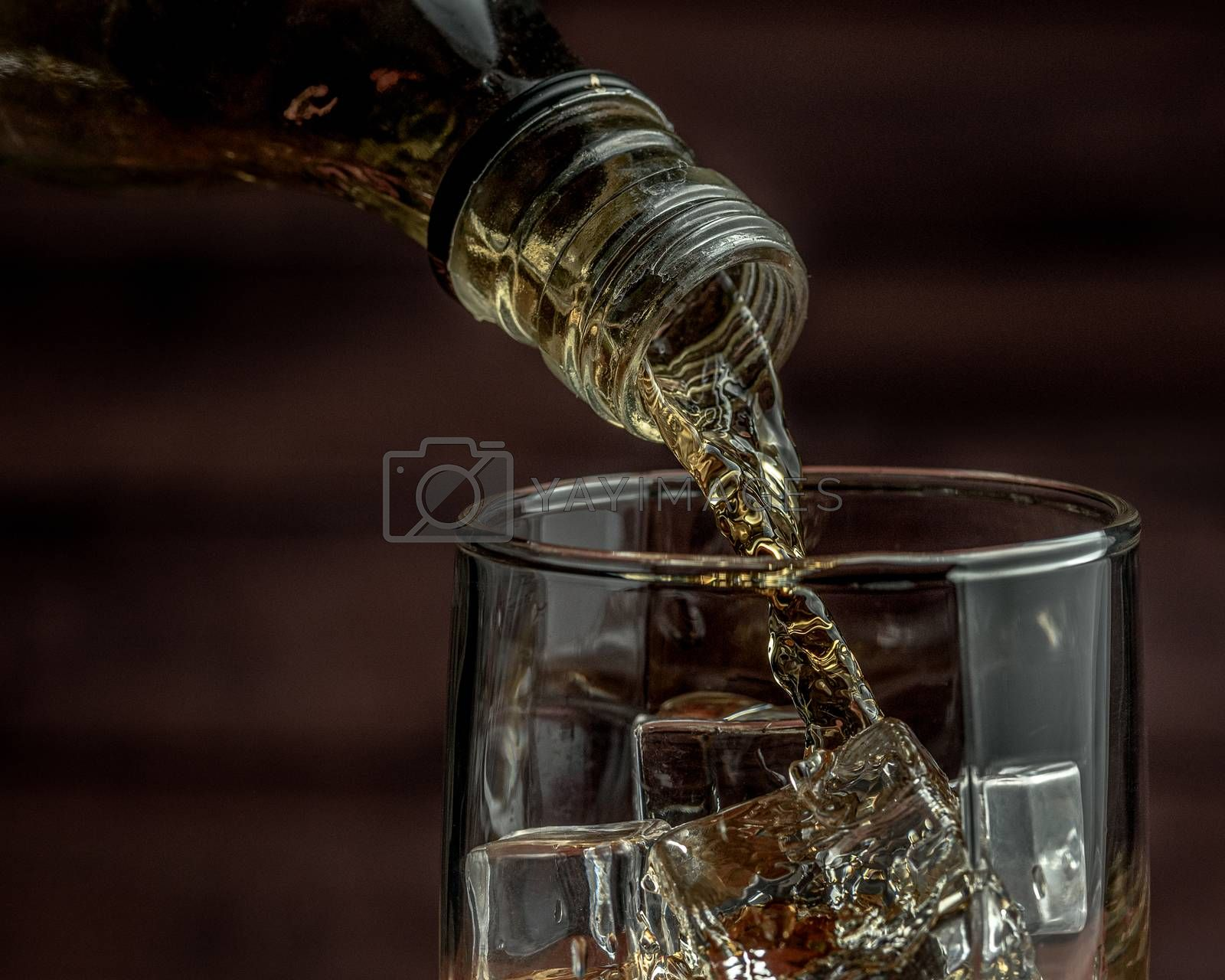 Royalty free image of Whiskey pours from a bottle into a glass by VladimirZubkov