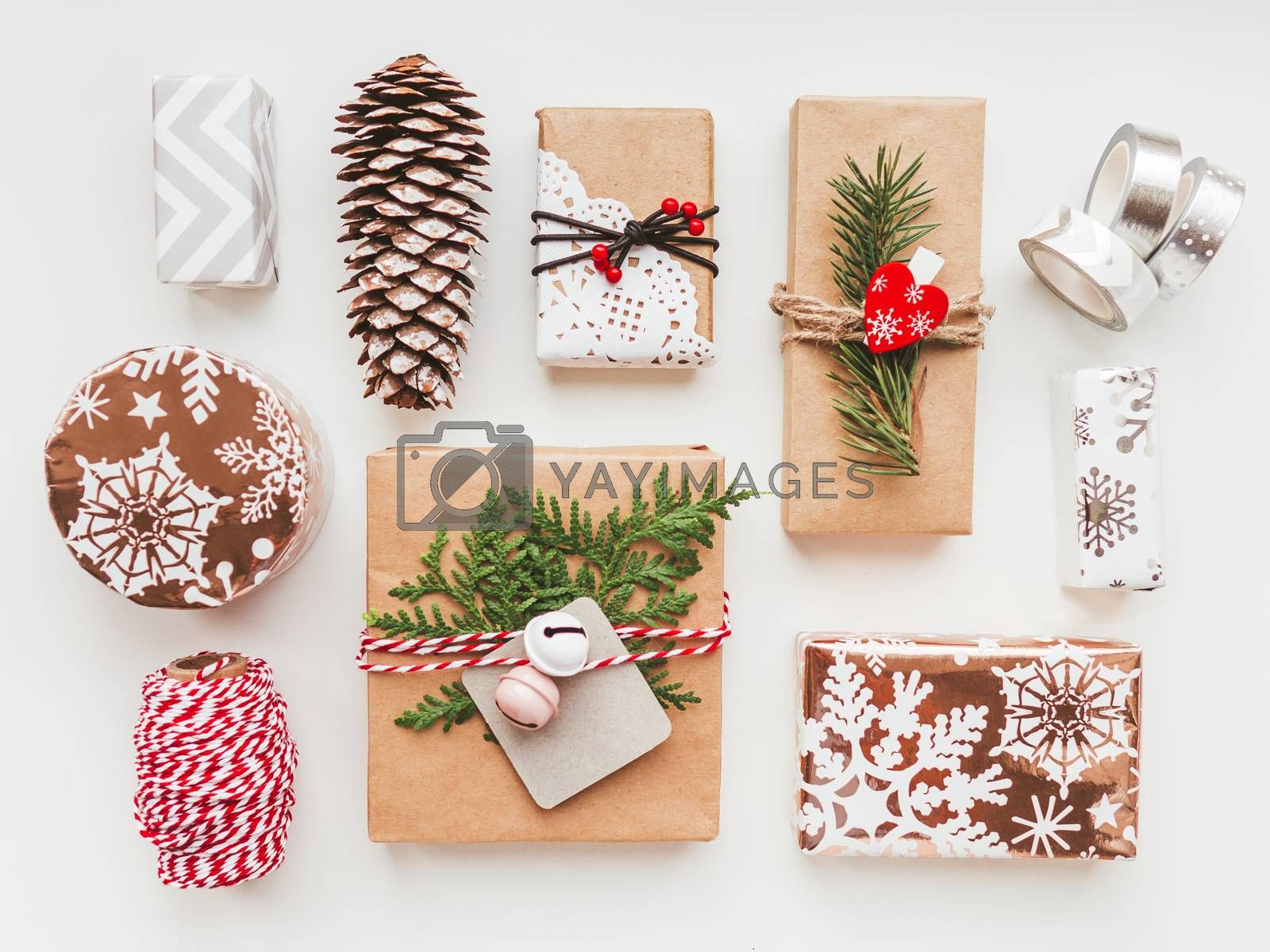 Christmas DIY presents wrapped in craft paper with fir tree twigs and red heart and bells. Top view on decorations on New Year gifts. Festive background. Winter holiday spirit.